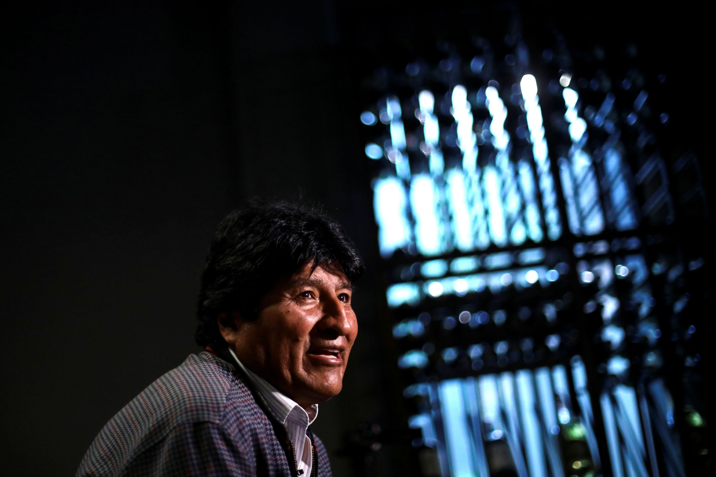 Former Bolivian President Evo Morales is shown wearing a jacket with light streaming through a window in the distance.