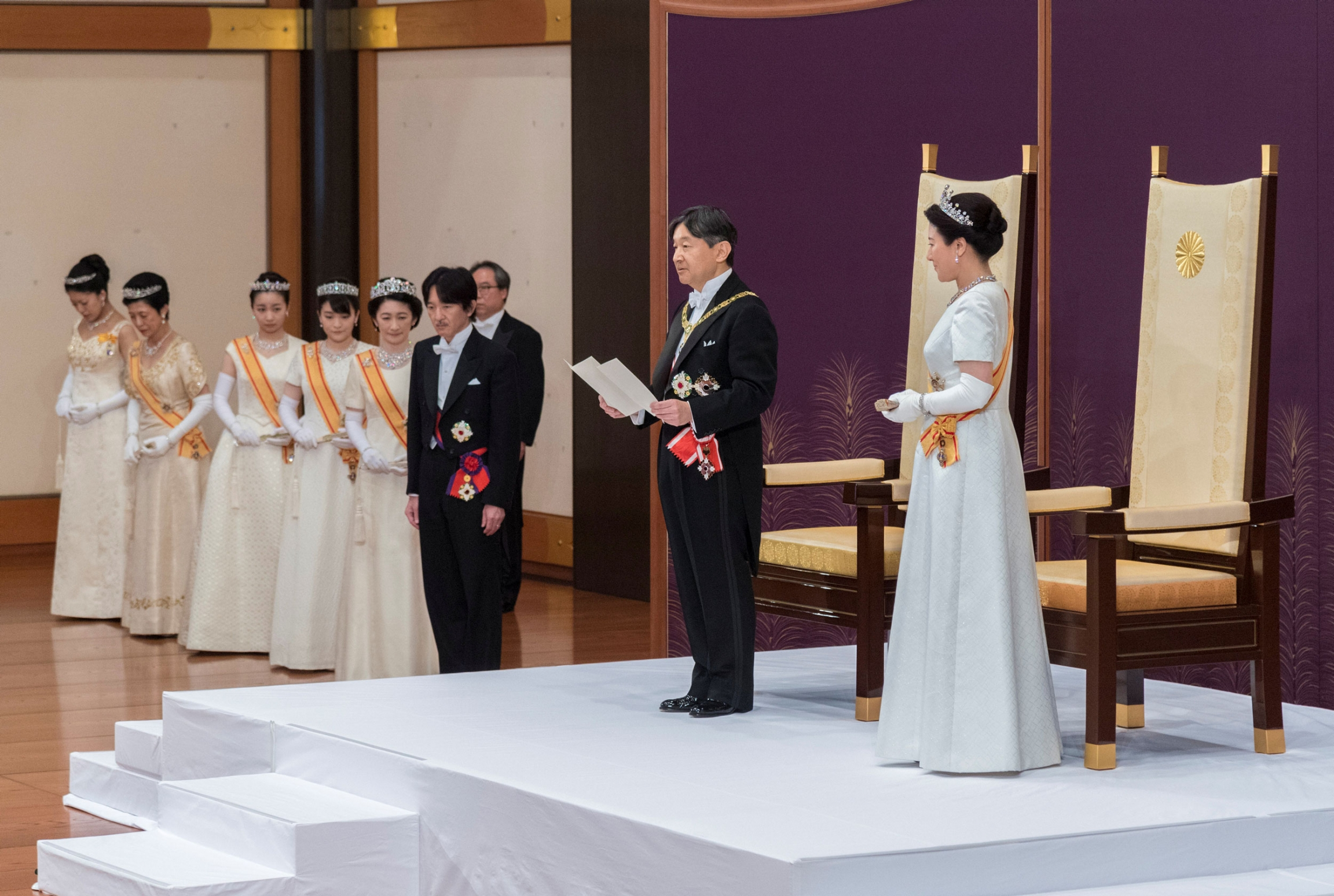 Japan's Emperor Naruhito, flanked by Empress Masako are shown standing on a white platform in front of tall-backed chairs.