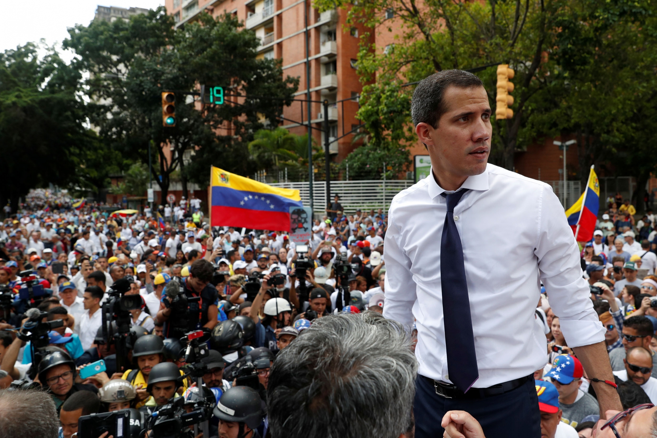 Venezuelan opposition leader Juan Guaidó is shown wearing a white shirt and tie in front of a large group of people.