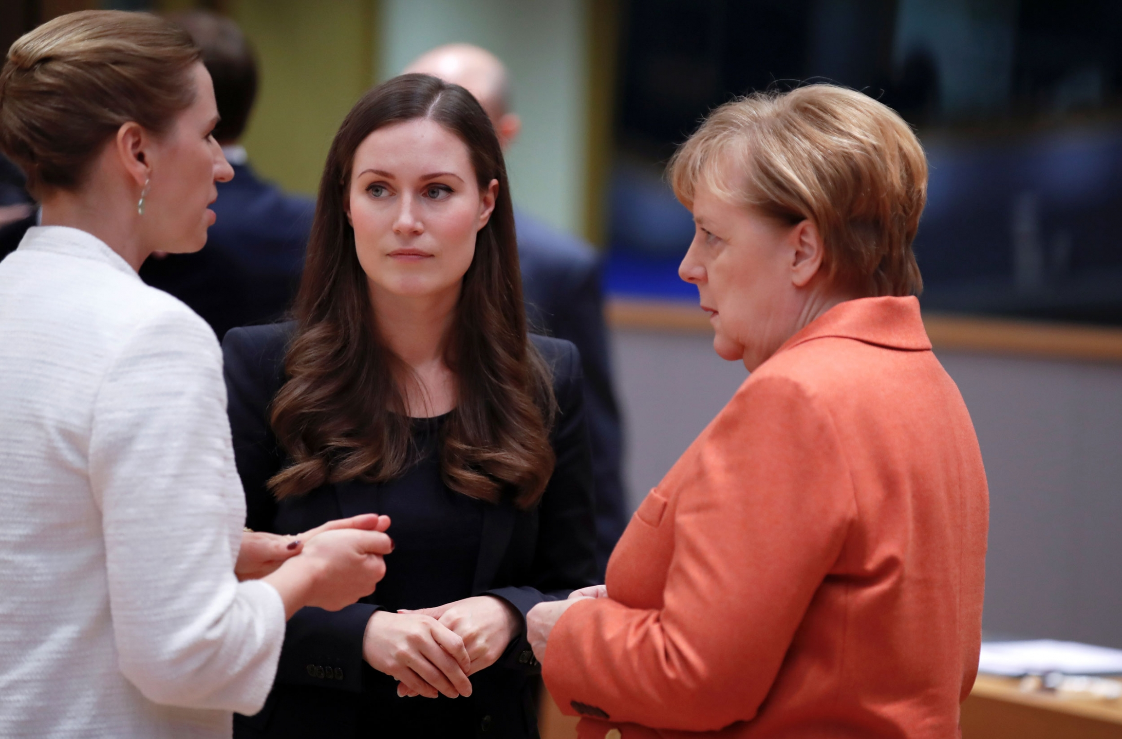 German Chancellor Angela Merkel, Finland's Prime Minister Sanna Marin and Denmark's Prime Minister Mette Frederiksen are shown standing, facing each other and talking.