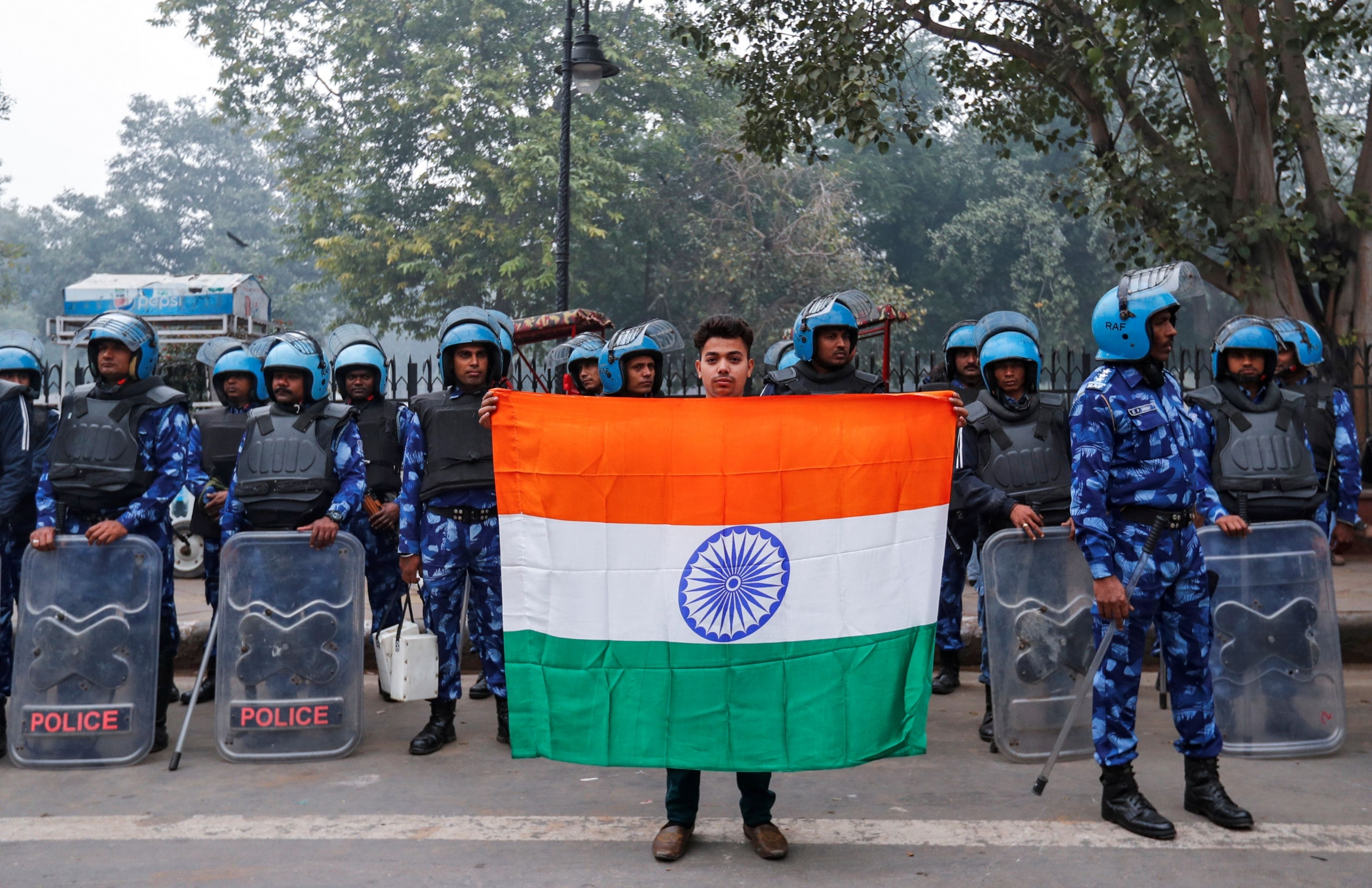 A man holds Indian flag in front of police wearing blue uniforms.