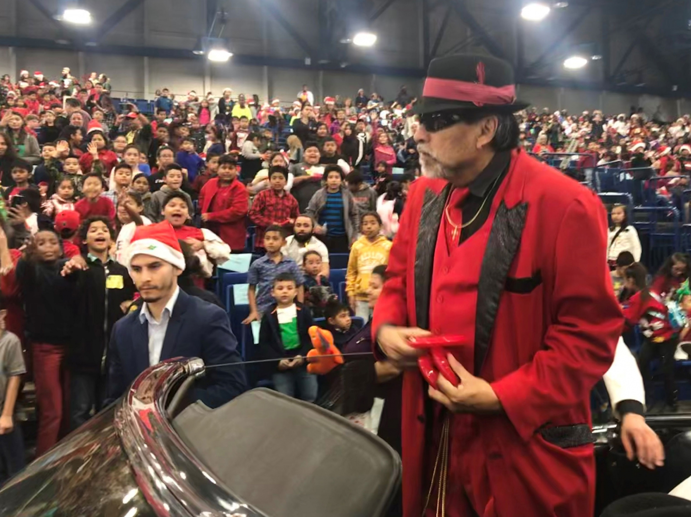 Pancho Claus is shown in a red jacket and black hat standing in a car with a large crowd behind him.