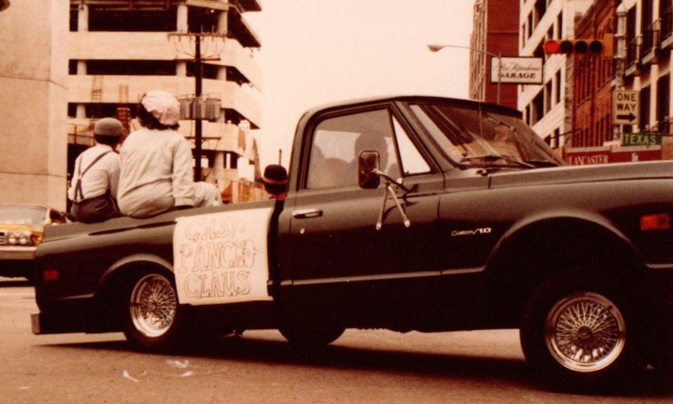A pickup truck is shown with three people sitting in the back.