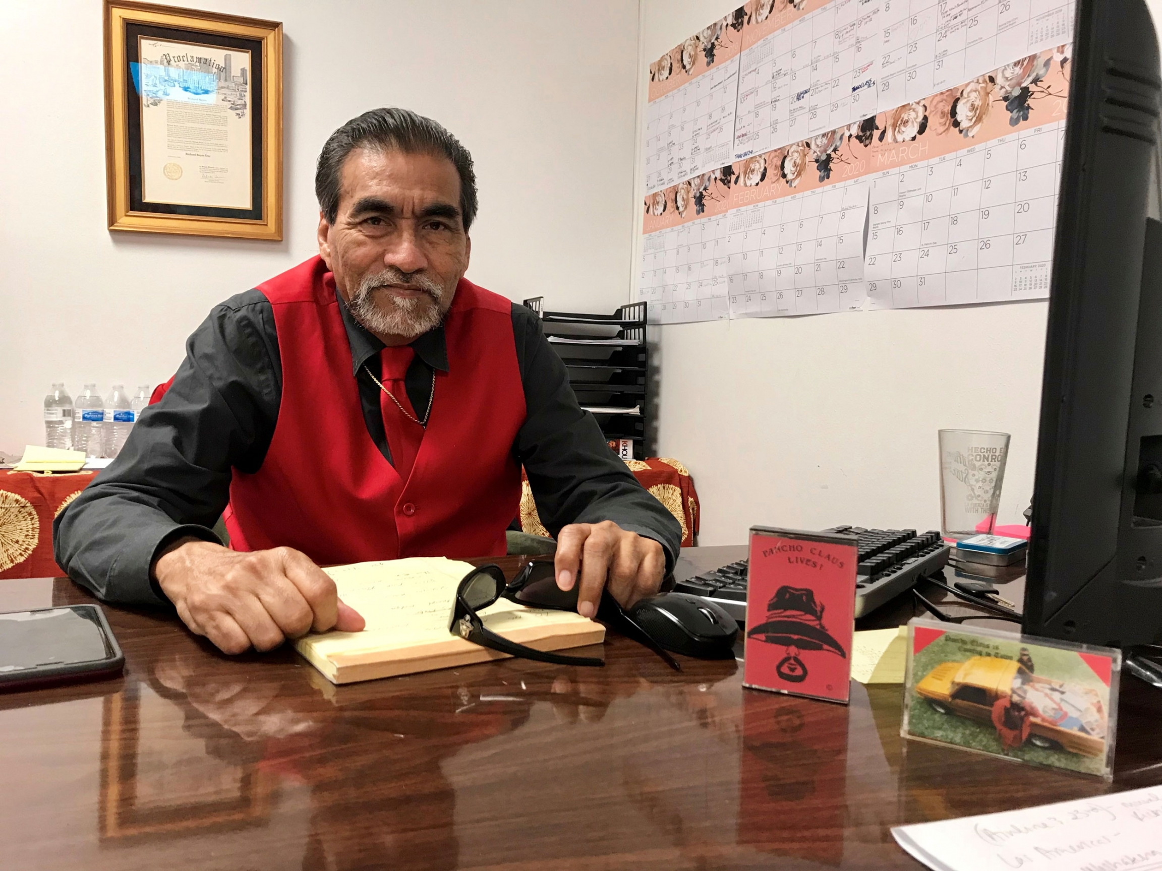 Richard Reyes is shown wearing a red vest and tie while sitting at his desk