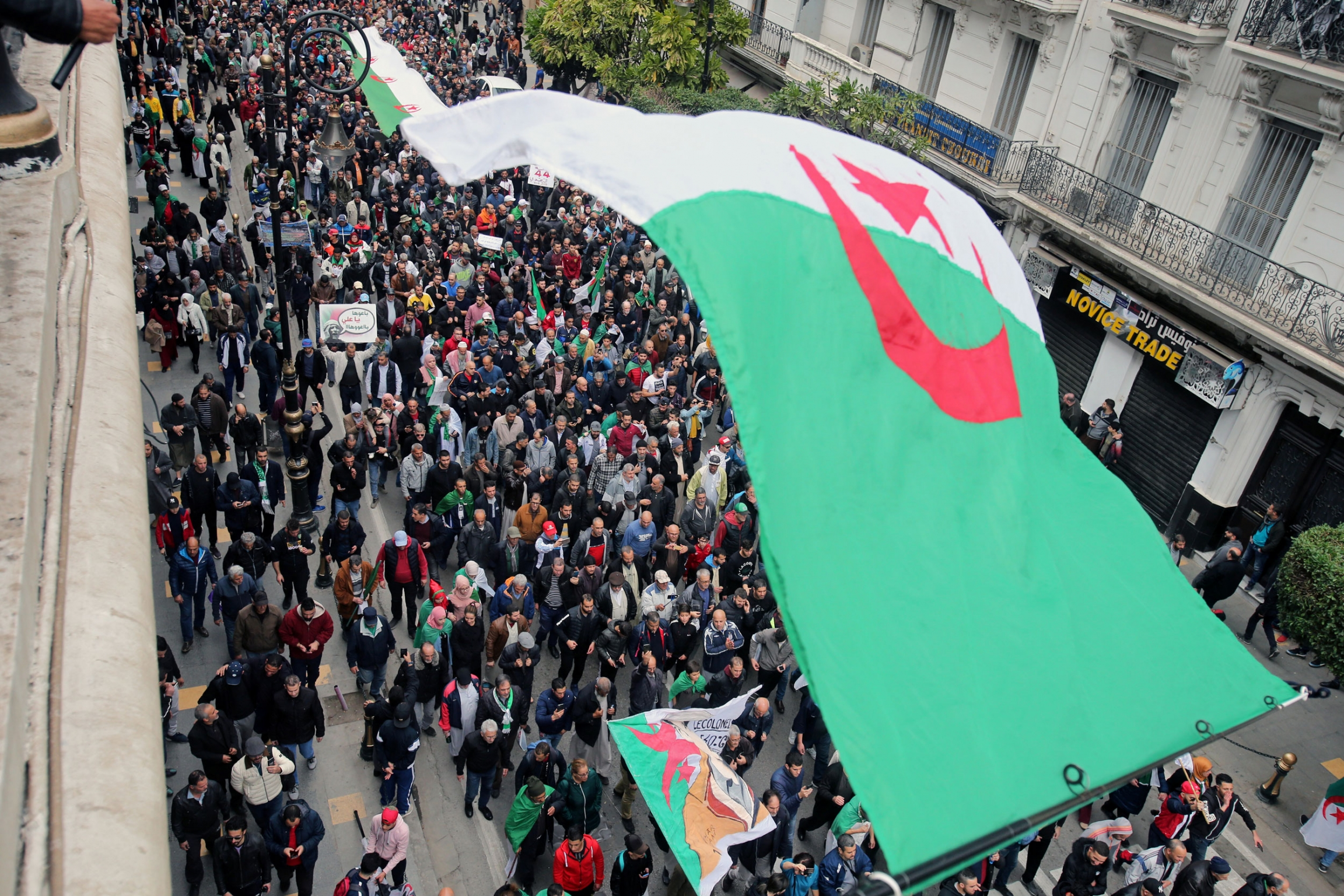 A street is shown filled with people and an Algerian flag is in the nearground.