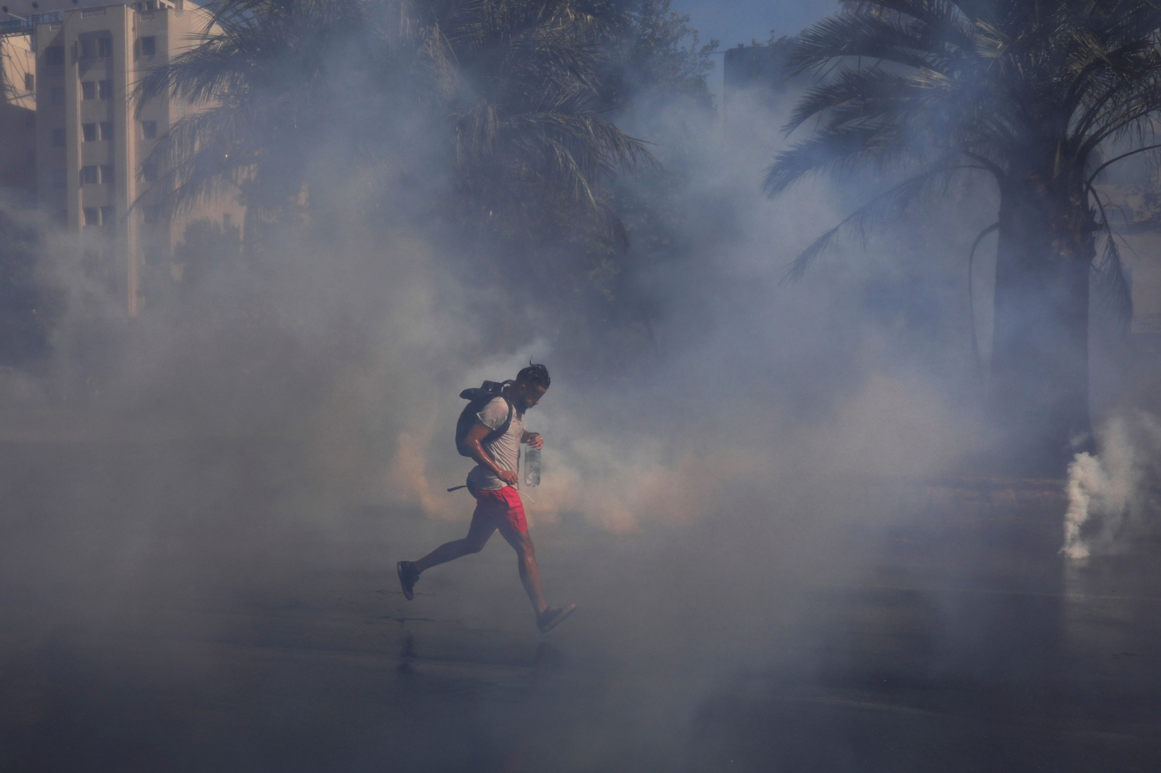 A demonstrator wearing red shorts and carrying a backpack, runs amid tear gas.