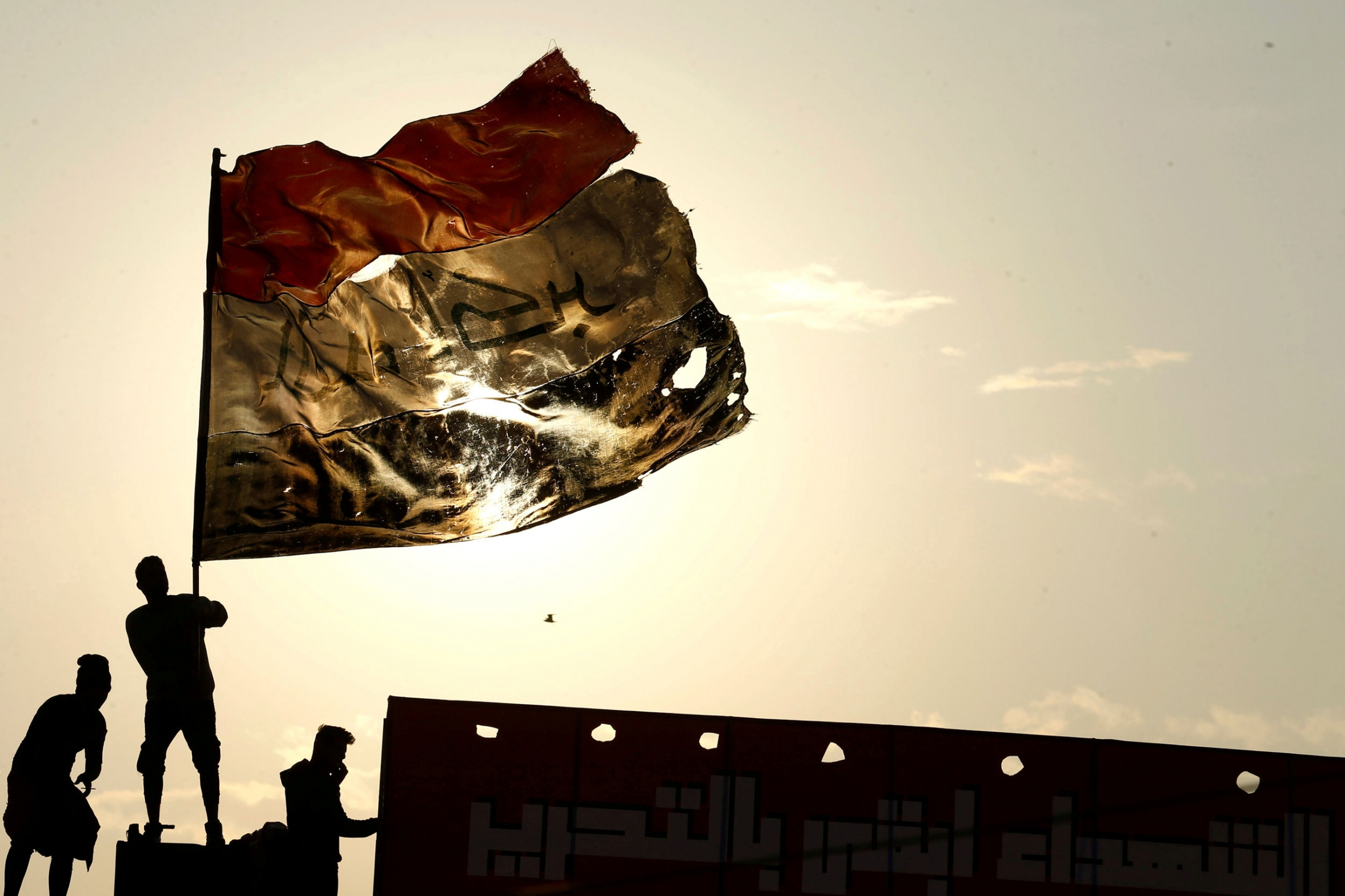 Three people are shown with one holding a large tattered Iraqi flag