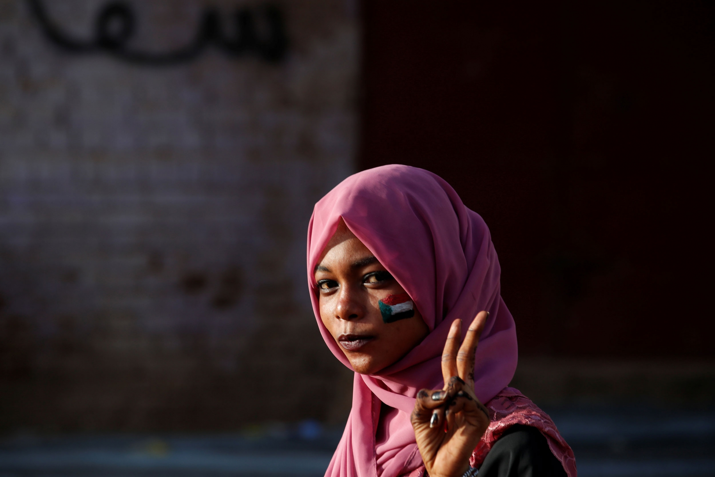 A woman is shown wearing a pink headscarf and with a Sudanese flag painted on her cheek.