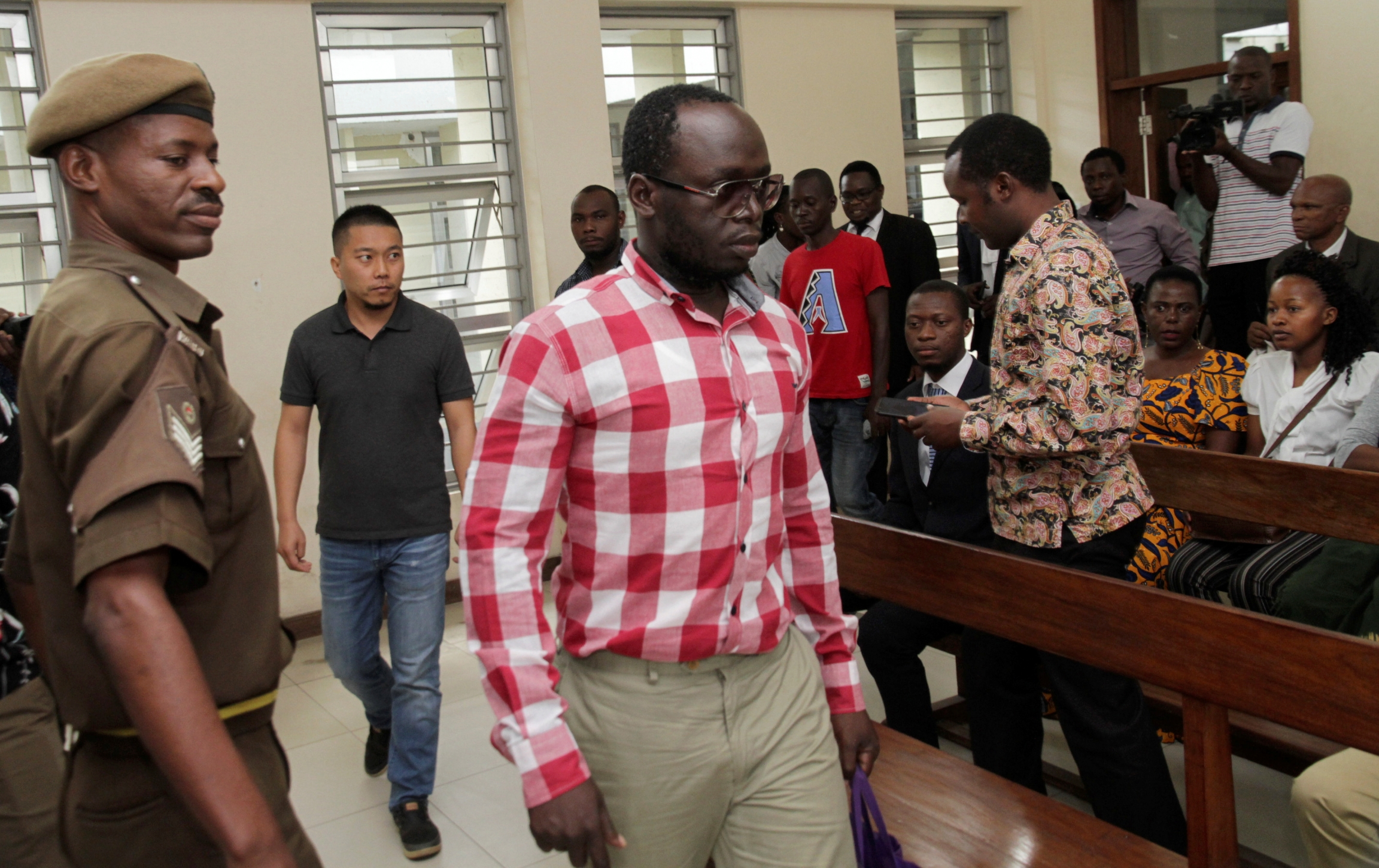 Erick Kabendera wears a white and red shirt and leaves a court room flanked by police