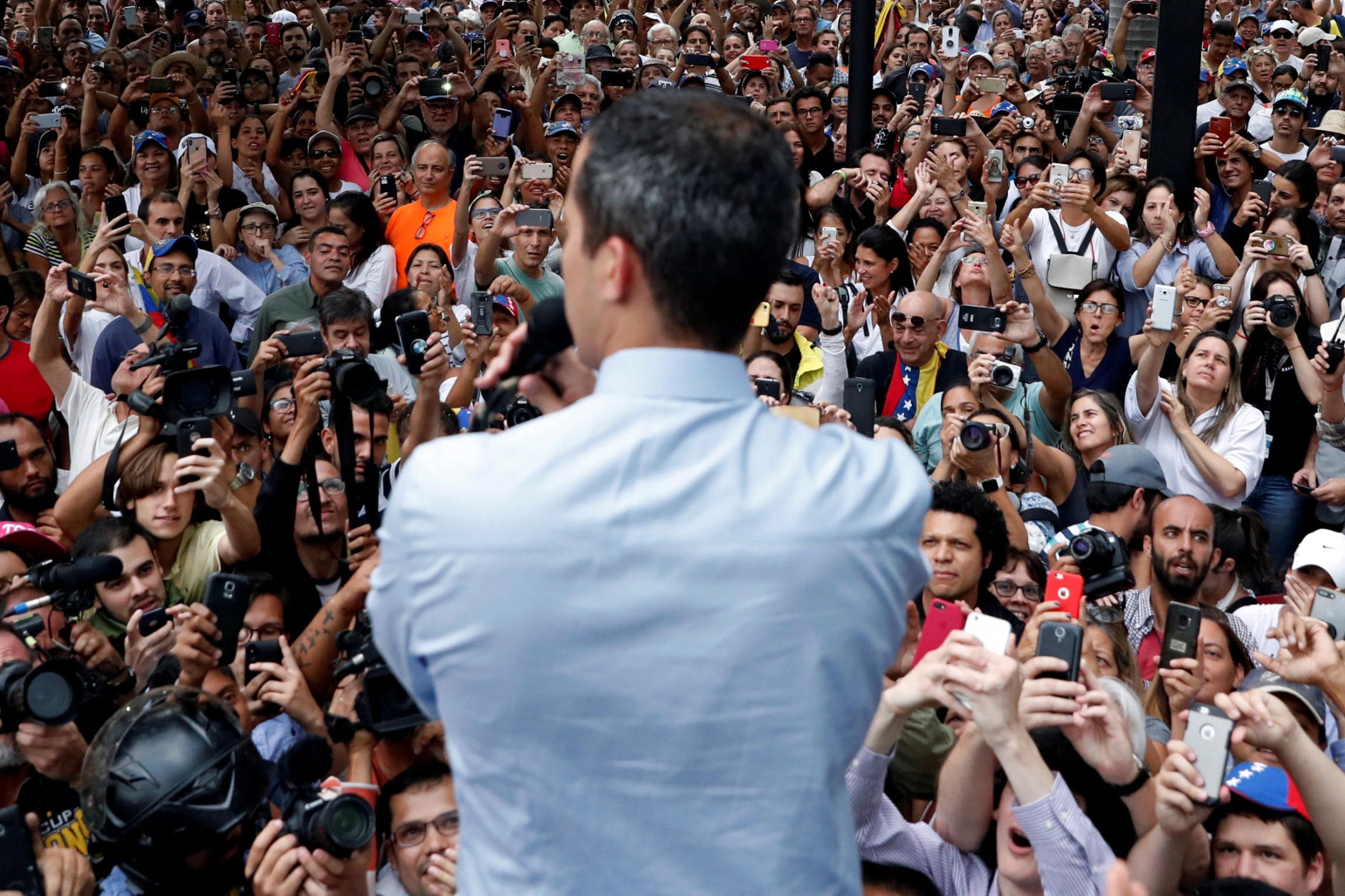 Venezuelan opposition leader Juan Guaidó is shown from behind while looking out on a large crowd.