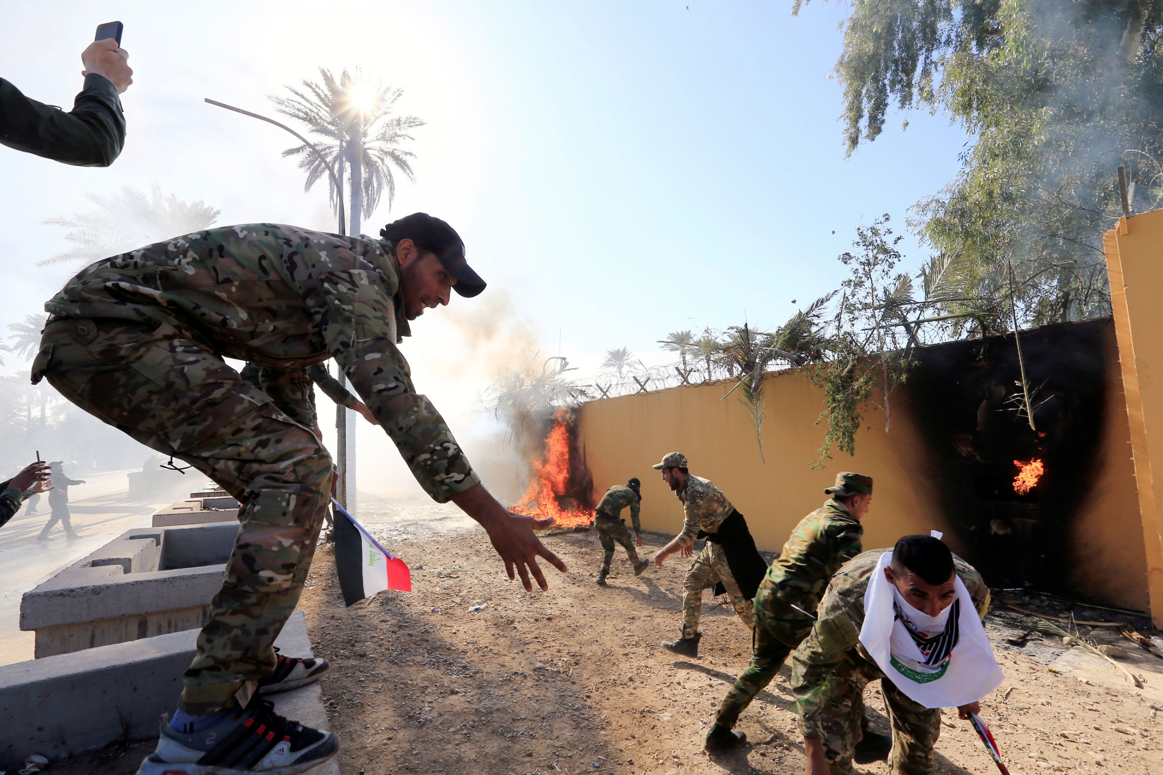 Several men are shown wearing military fatigues outside of a khaki-colored wall that has been set on fire.