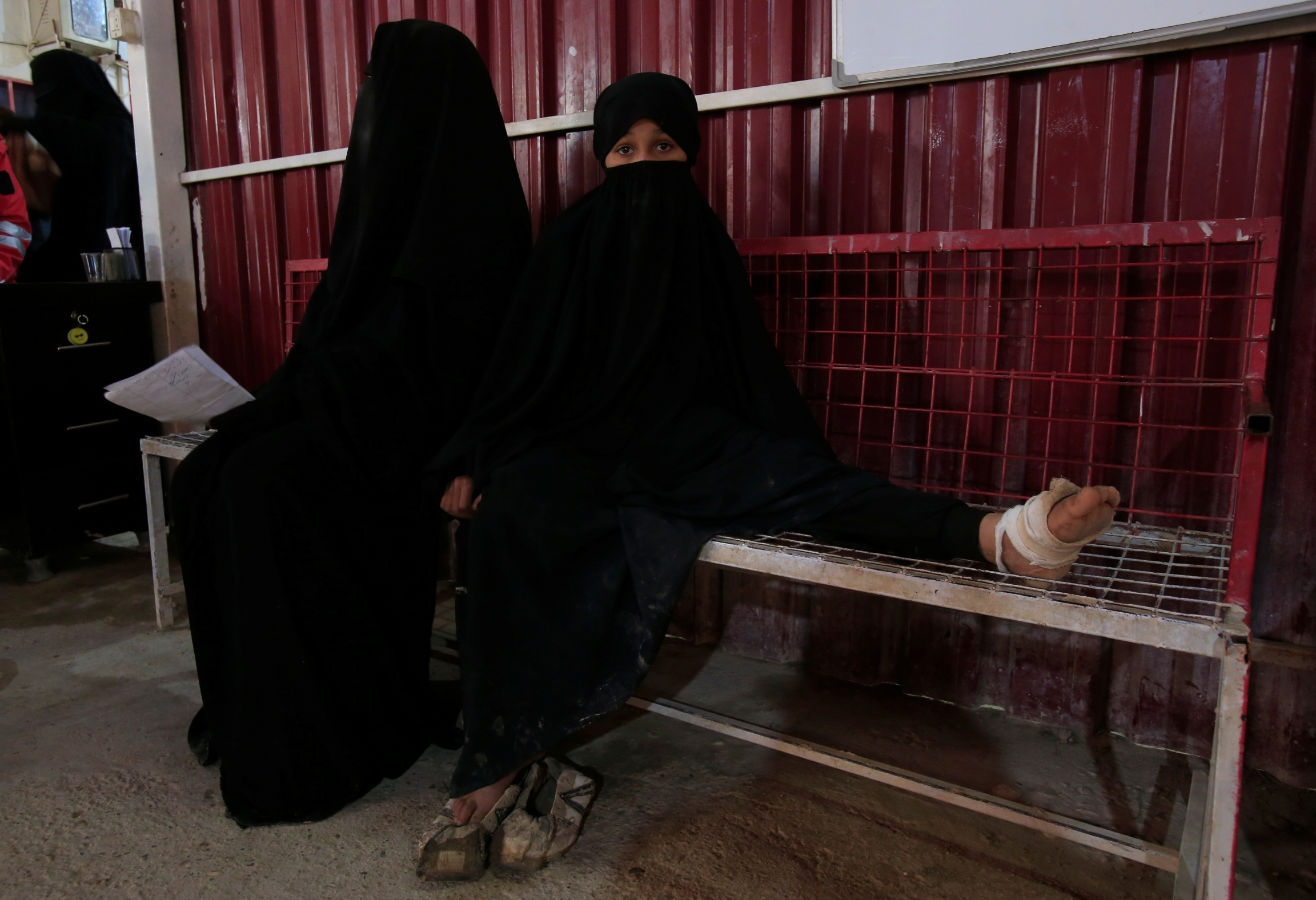 Two girls wearing black clothing sit on a bench in a clinic, one has a wounded foot wrapped in bandage