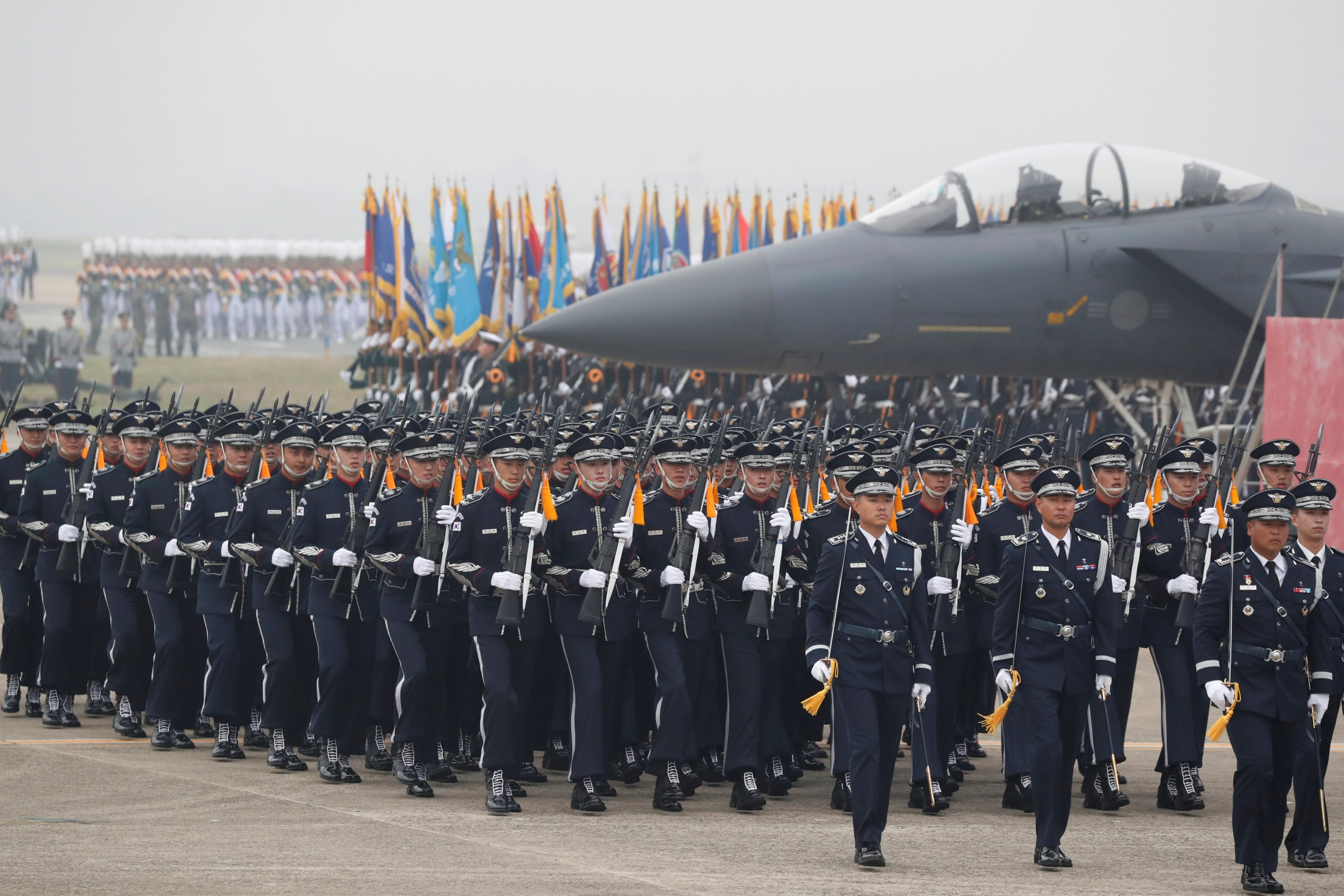 South Korean Army soldiers in black uniforms participate in a ceremony to mark the 71st anniversary of Armed Forces Day near military plane