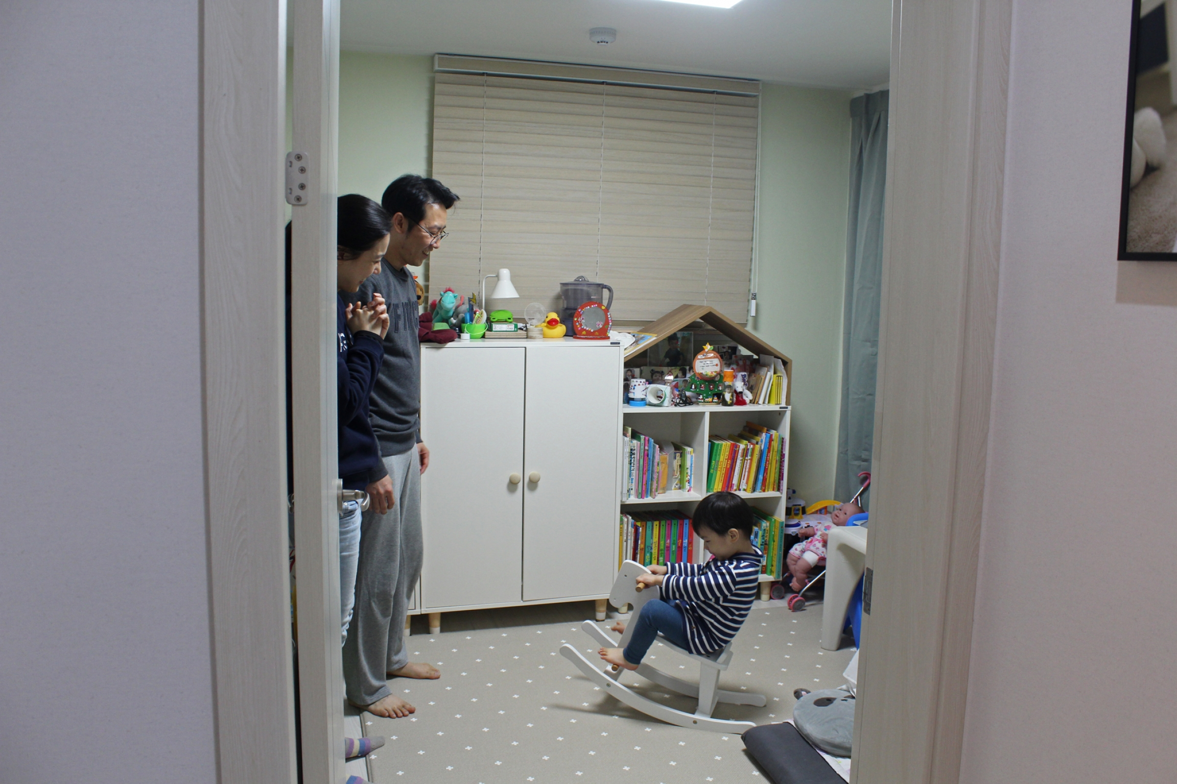 Seo Ji-hye and Cho Sung-won watch as their two-year-old son, Han-sol, rides a rocking horse in his bedroom in Seoul.