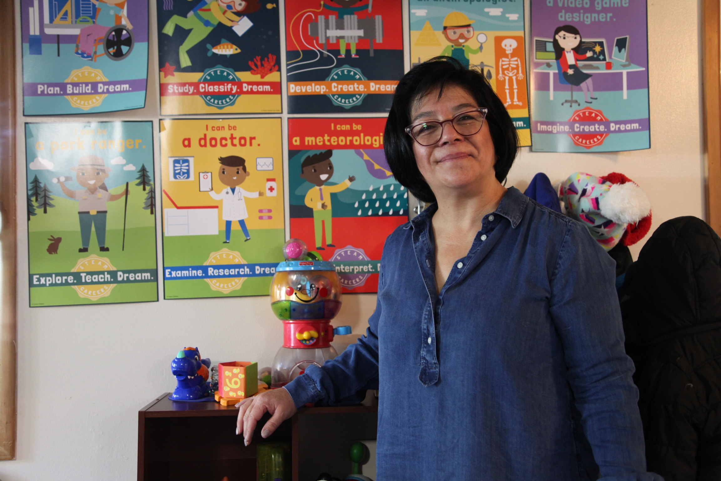 A woman stands in front of children's posters