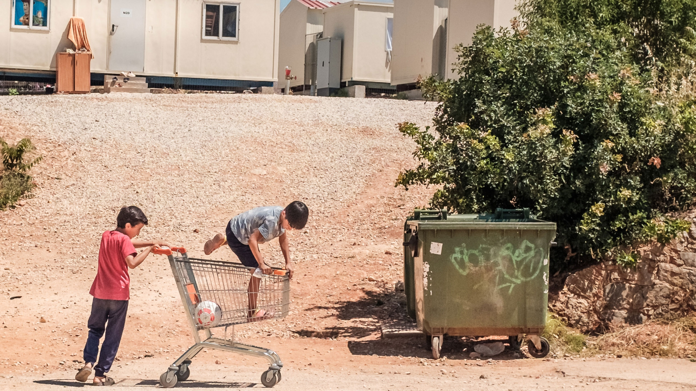 Two young children are shown playing with a grocery cart with container homes shown in the background.