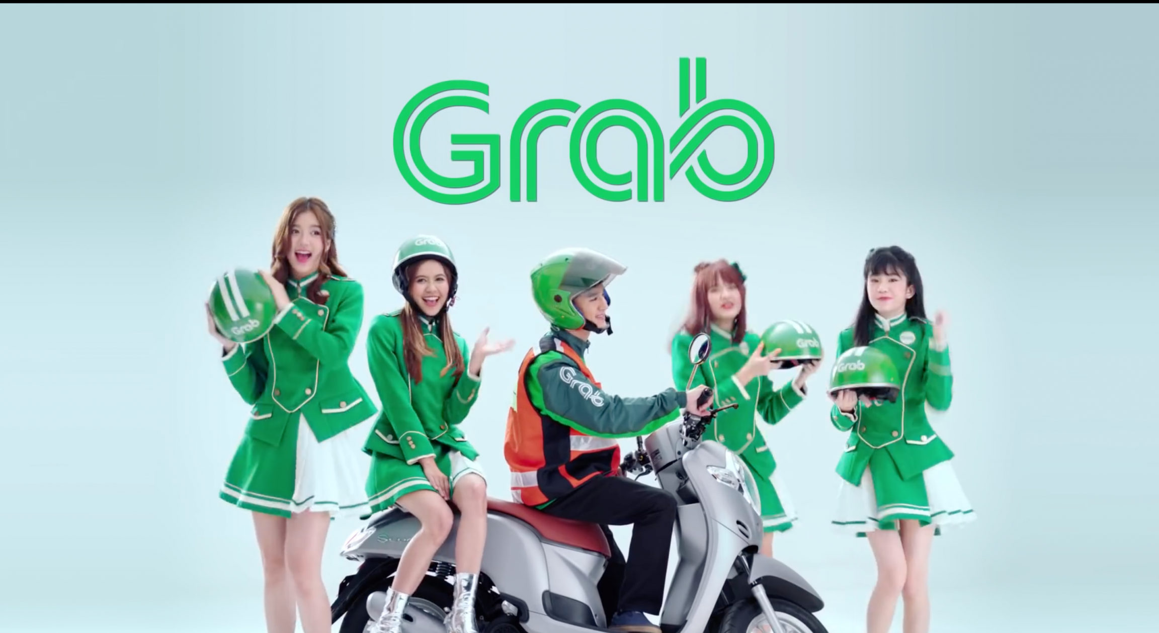 A popular girl band poses near a Grab driver wearing green uniform