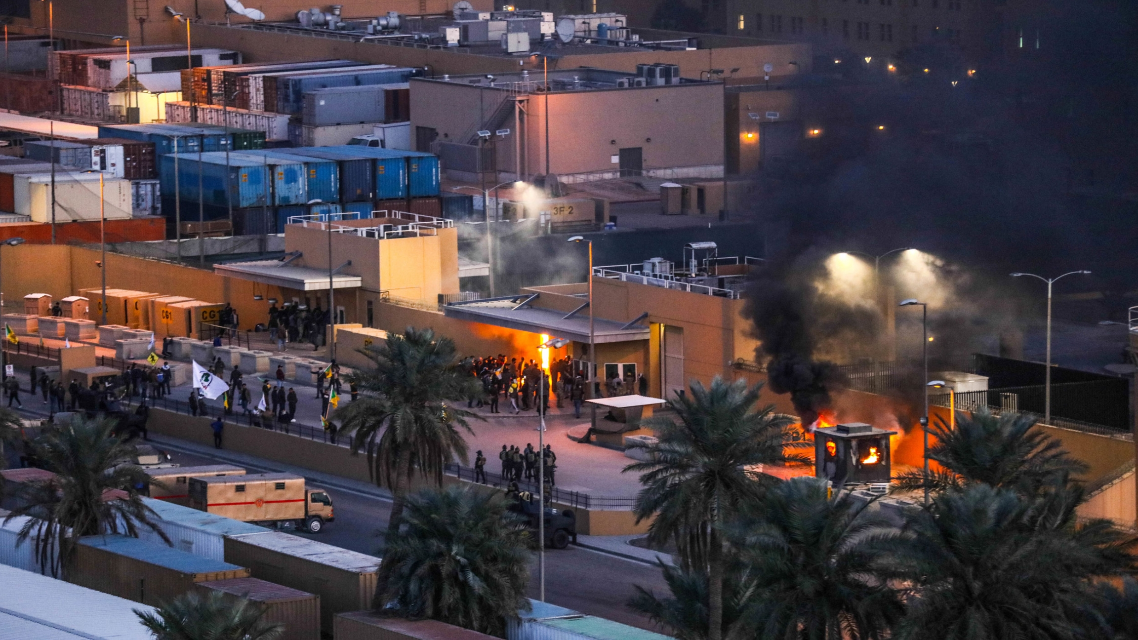 The khaki-color wall of the US Embassy in Baghdad is shown smoking from two fires set by a group of demonstrators.