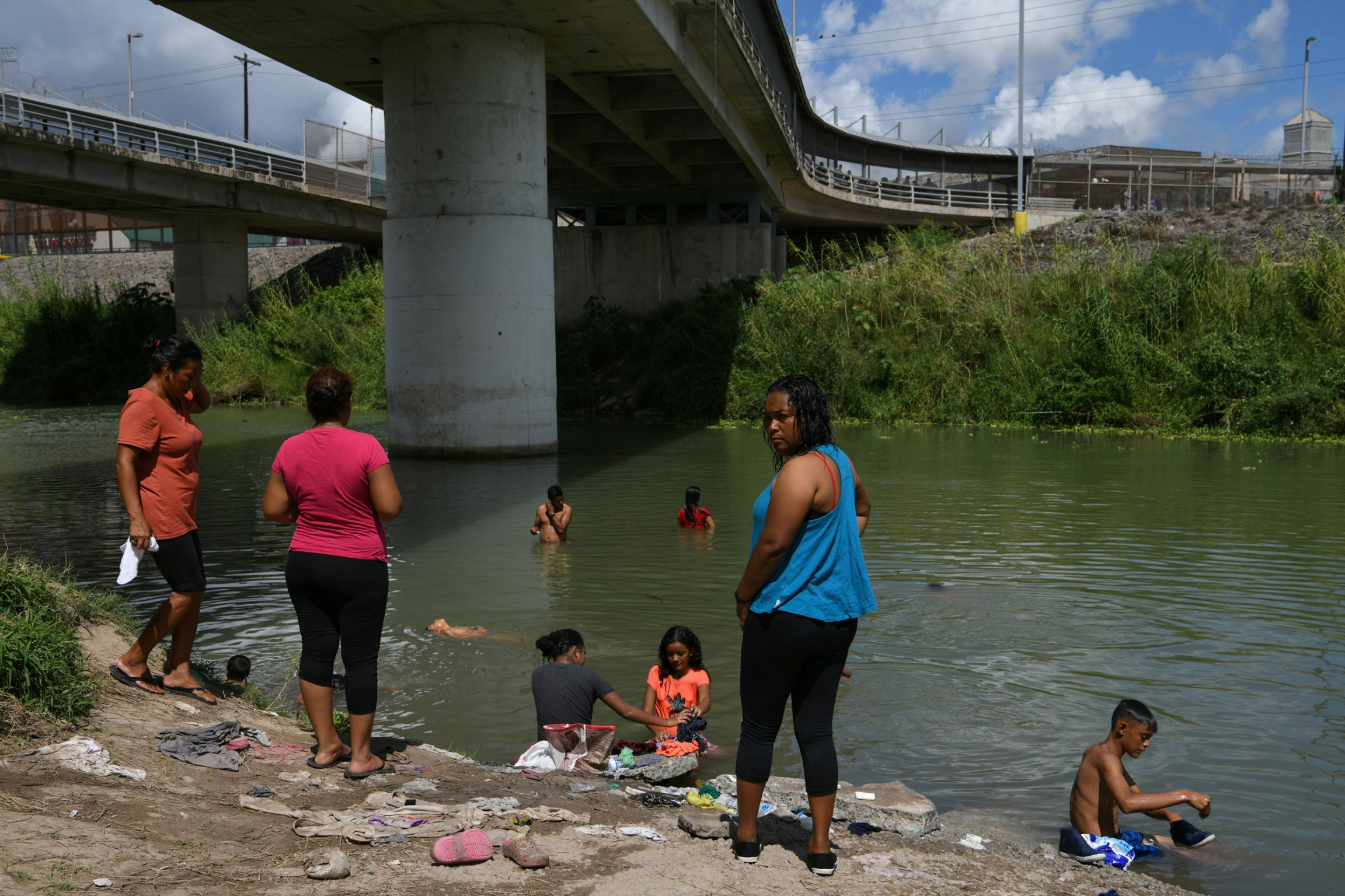 Several people are shown standing on the shore and in the Rio Grande river under a large bridge.