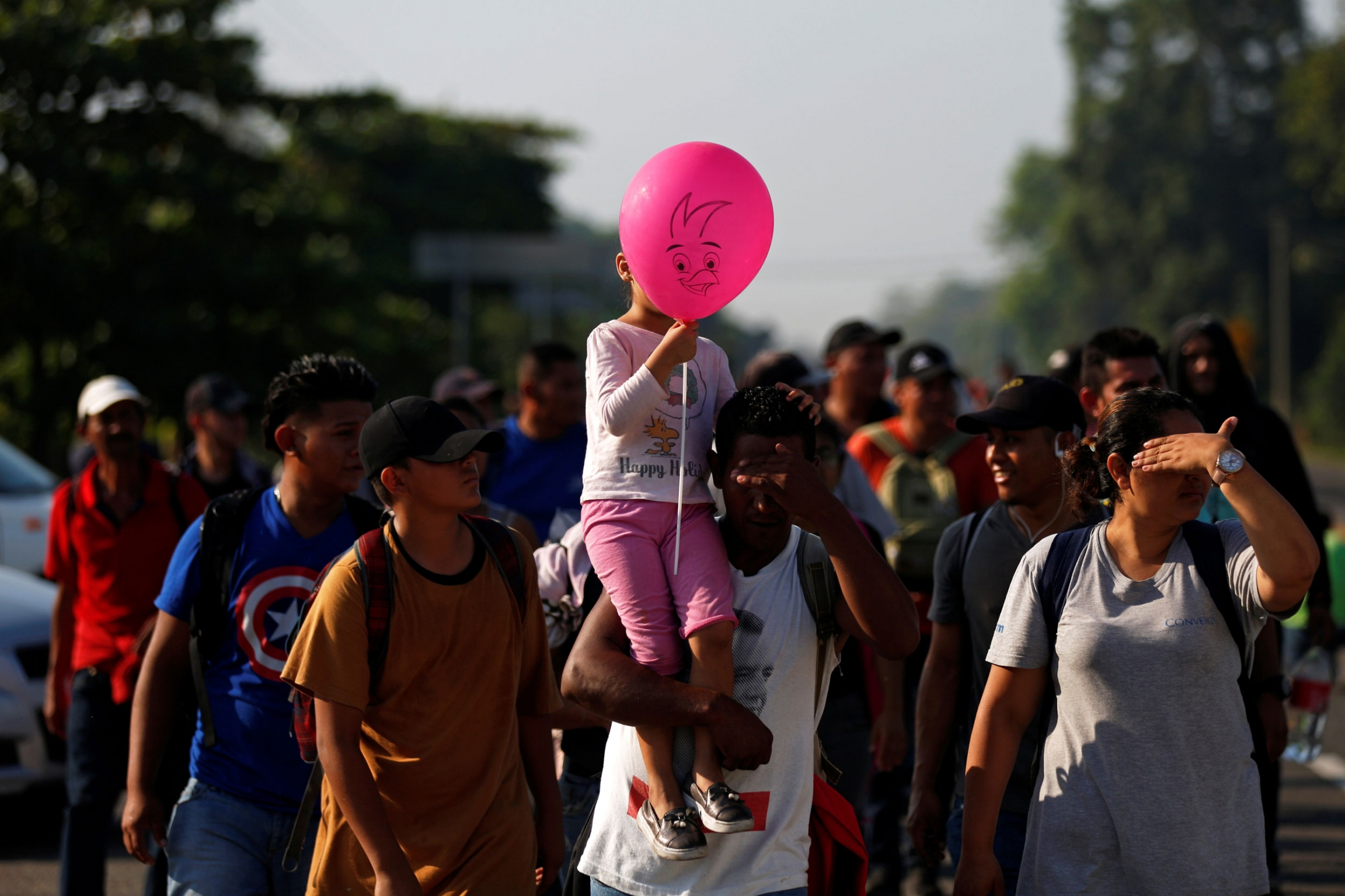 A large group of people are shown in the street walking and one person is carrying a young girl on their shoulder who has a pink balloon.