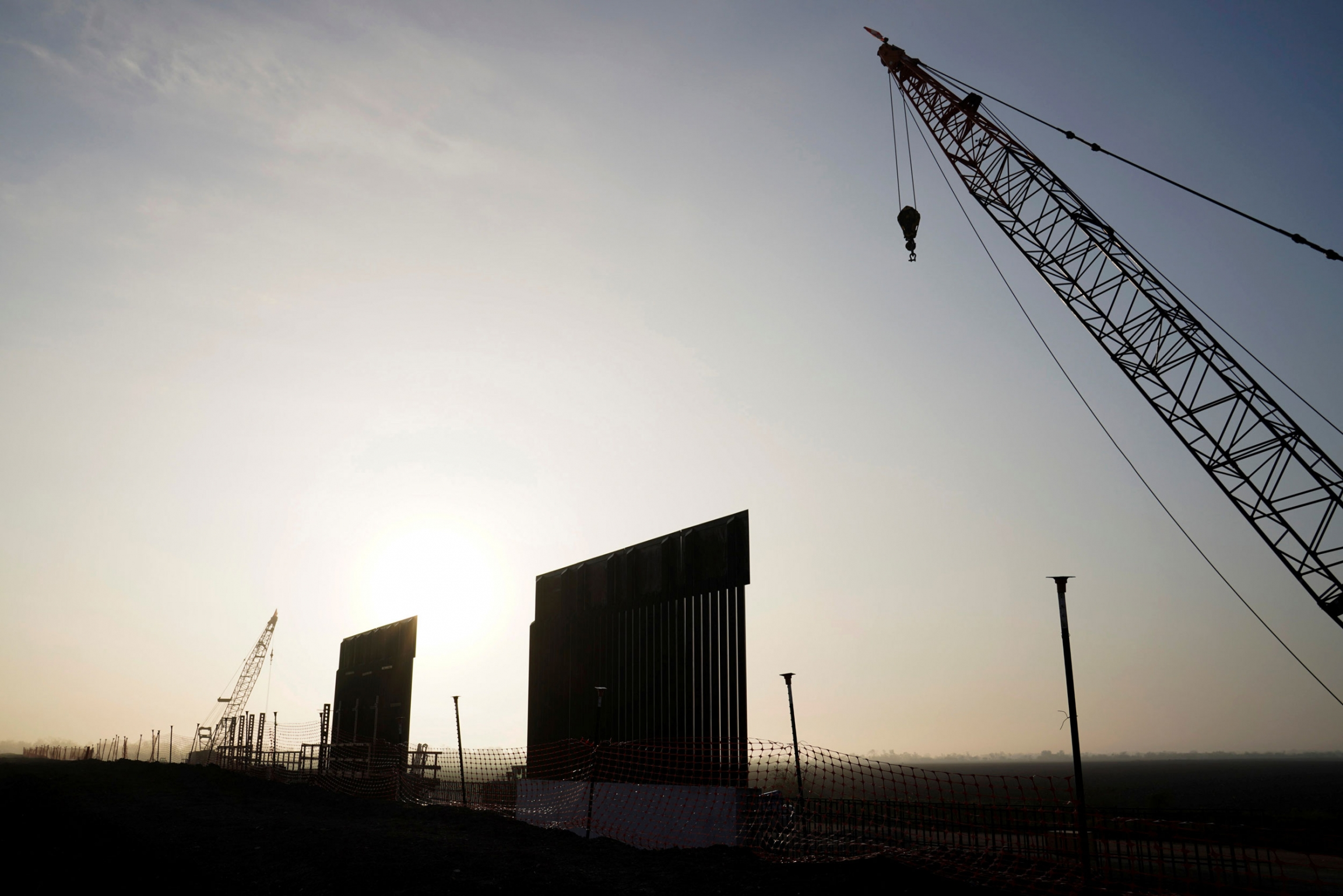 Two segments of the border wall are shown standing against a setting sun with a adjacent crane.