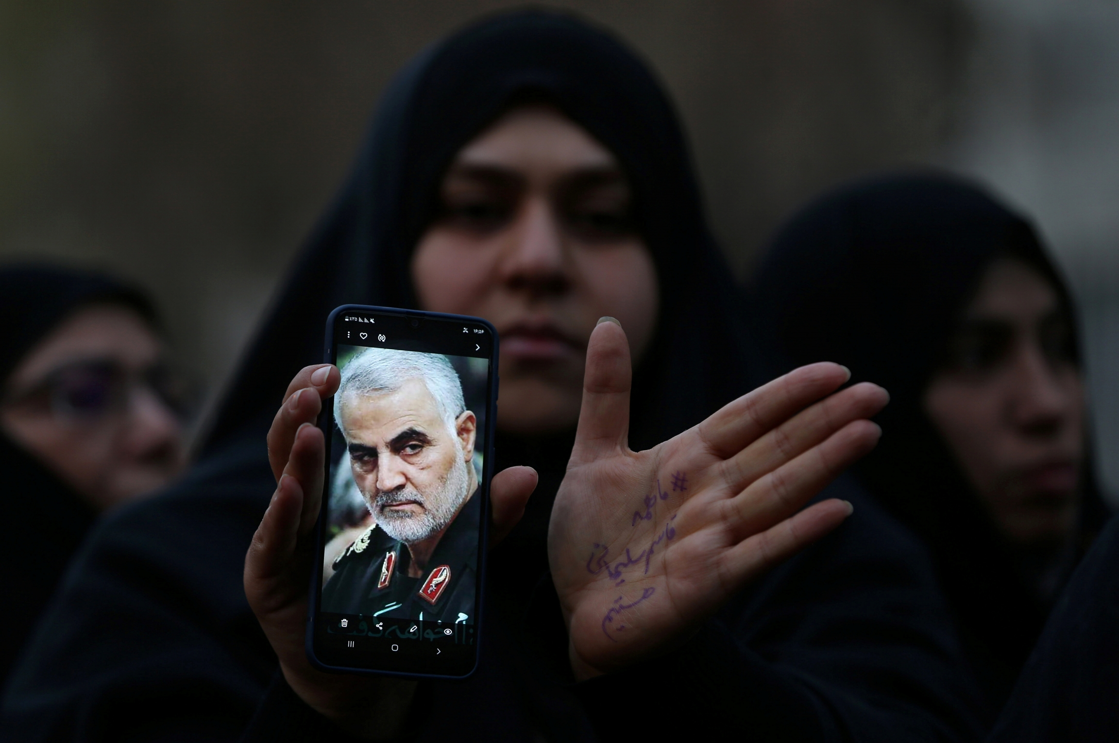 A woman wearing an abaya holds a cellphone with the photo of an Iranian military commander.