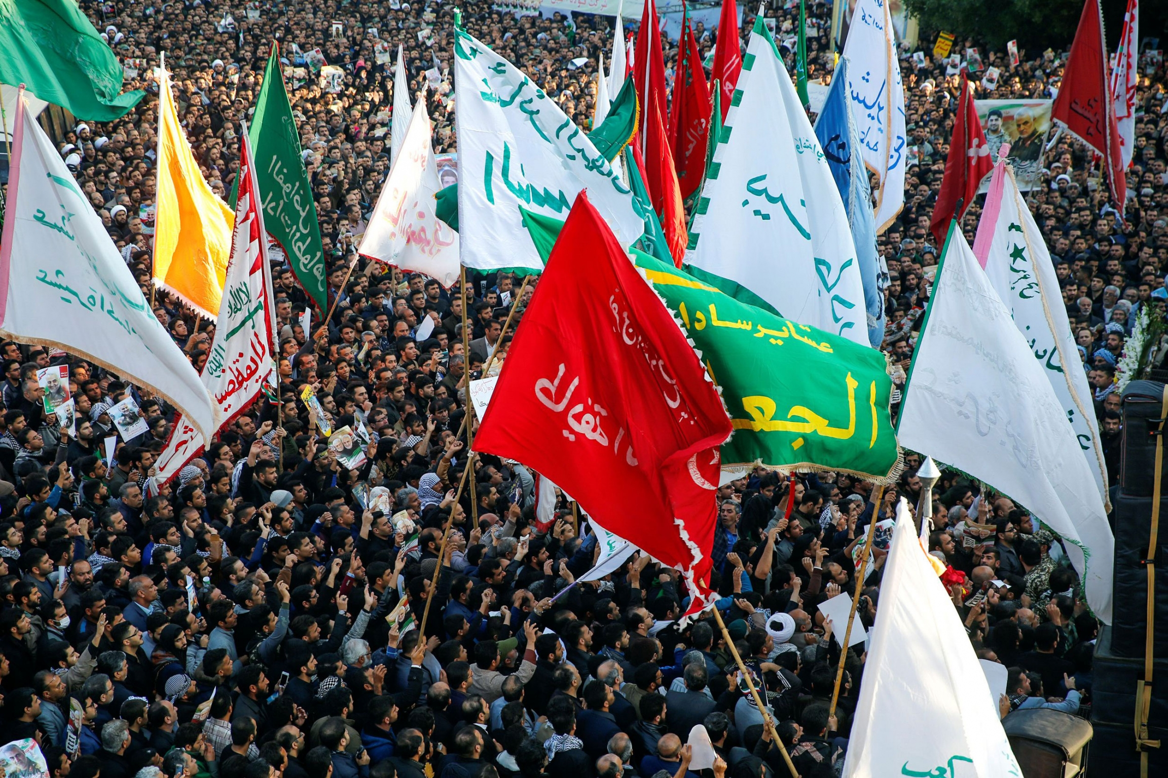 A large crowd of people are shown from above with dozens of flags waving.