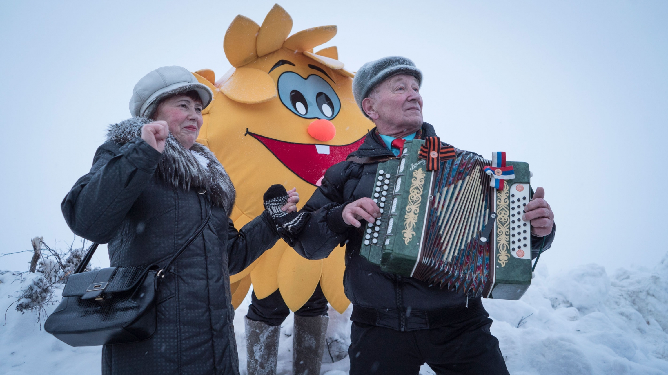 An older man is shown playing an accordion with a person dressed up in a sun costume stands behind him.