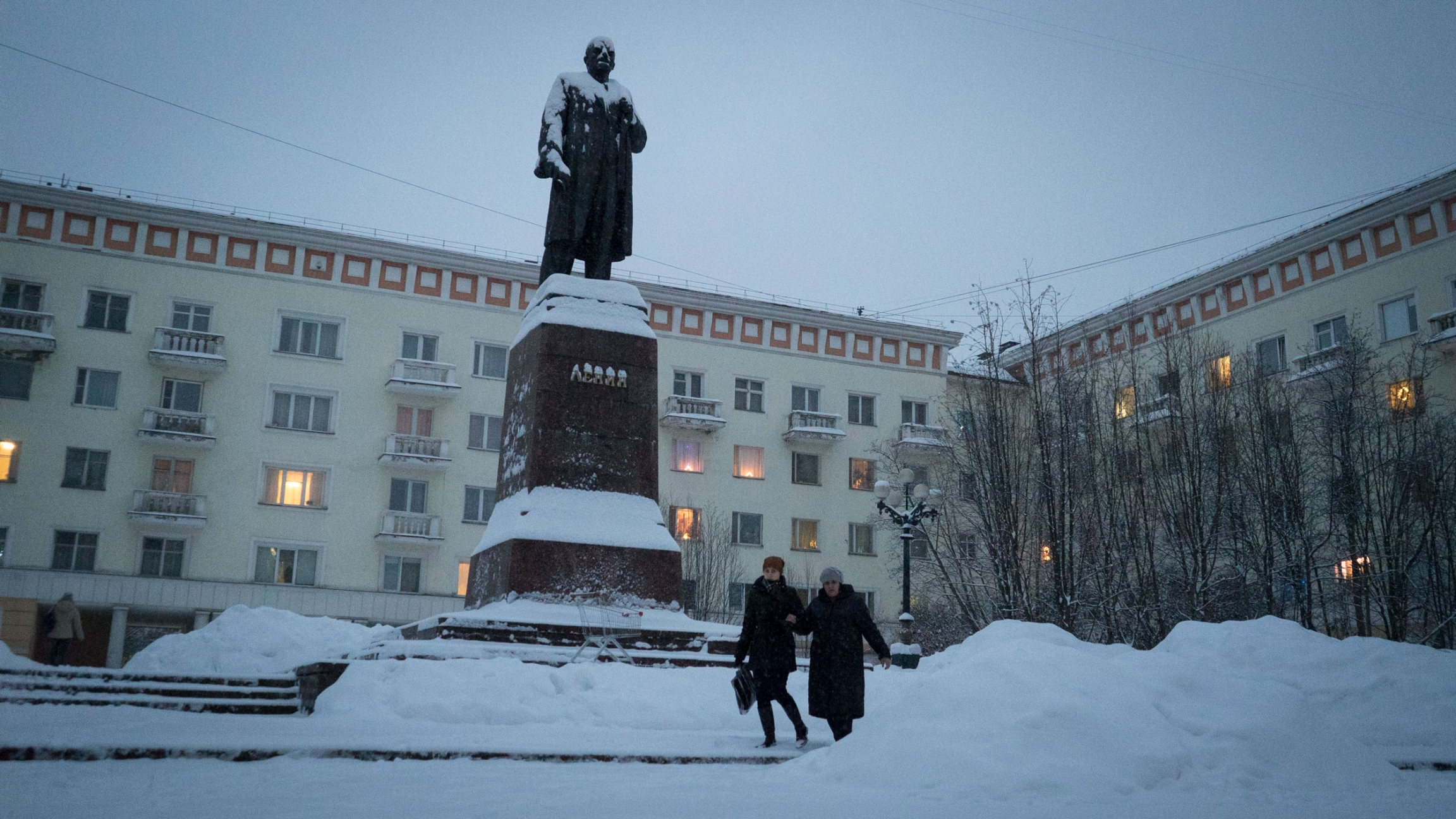 People walk past a snow covered statue of Soviet leader Vladimir Lenin.