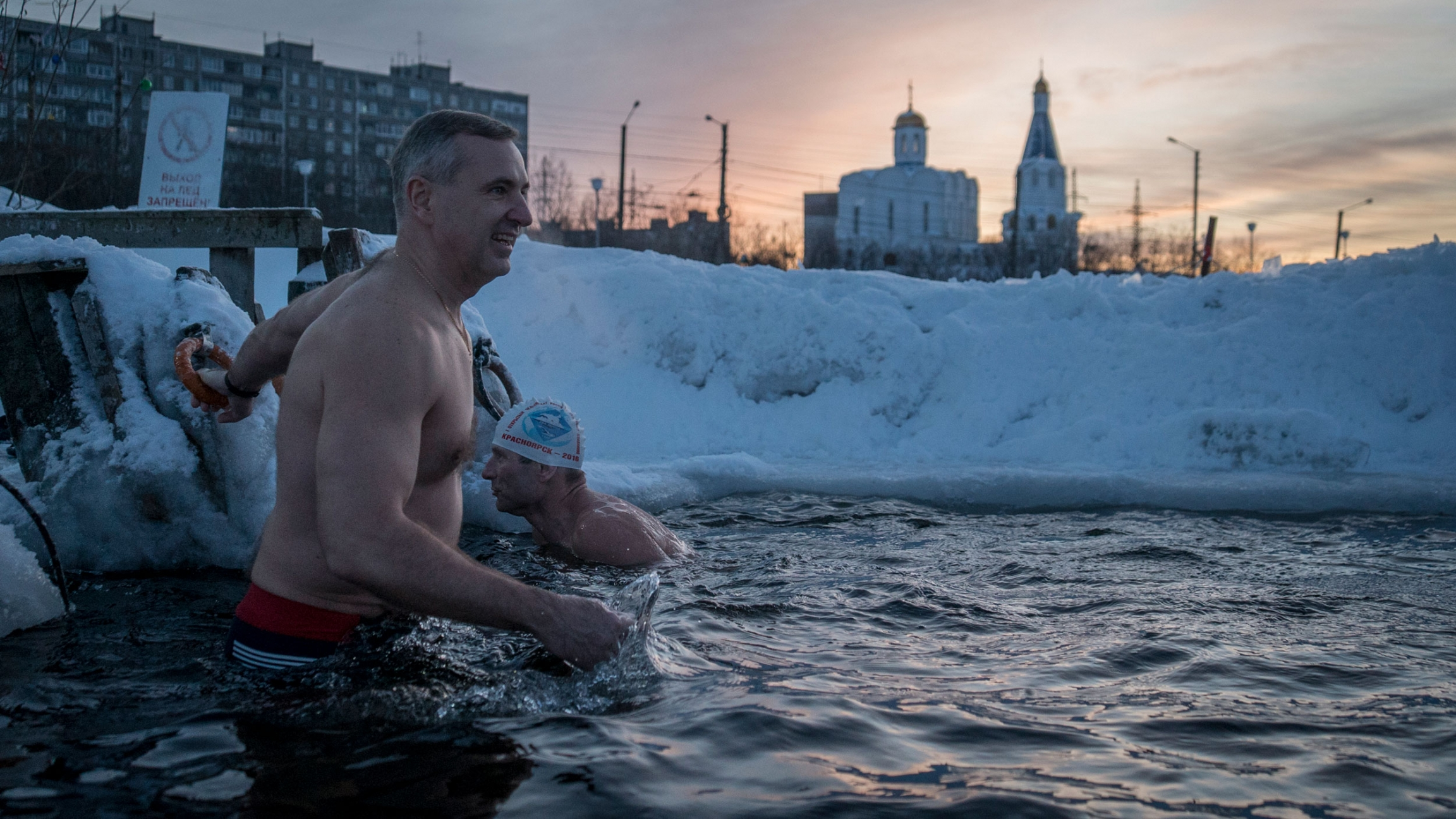 Alexander Spinul is shown without his shirt on and swims in an ice hole.