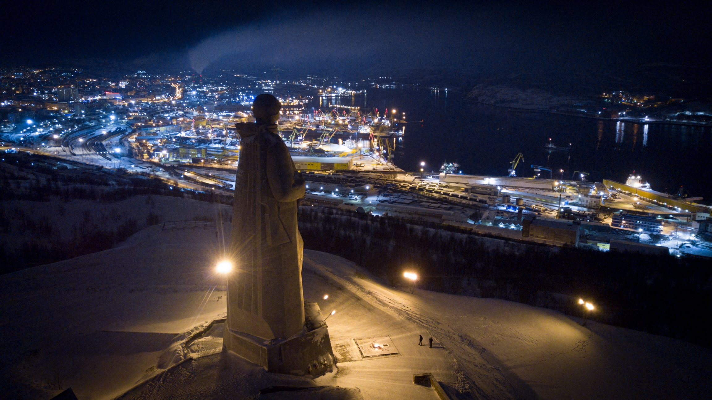 The Alyosha monument stands looking out over Murmansk off in the distance on a dark night.