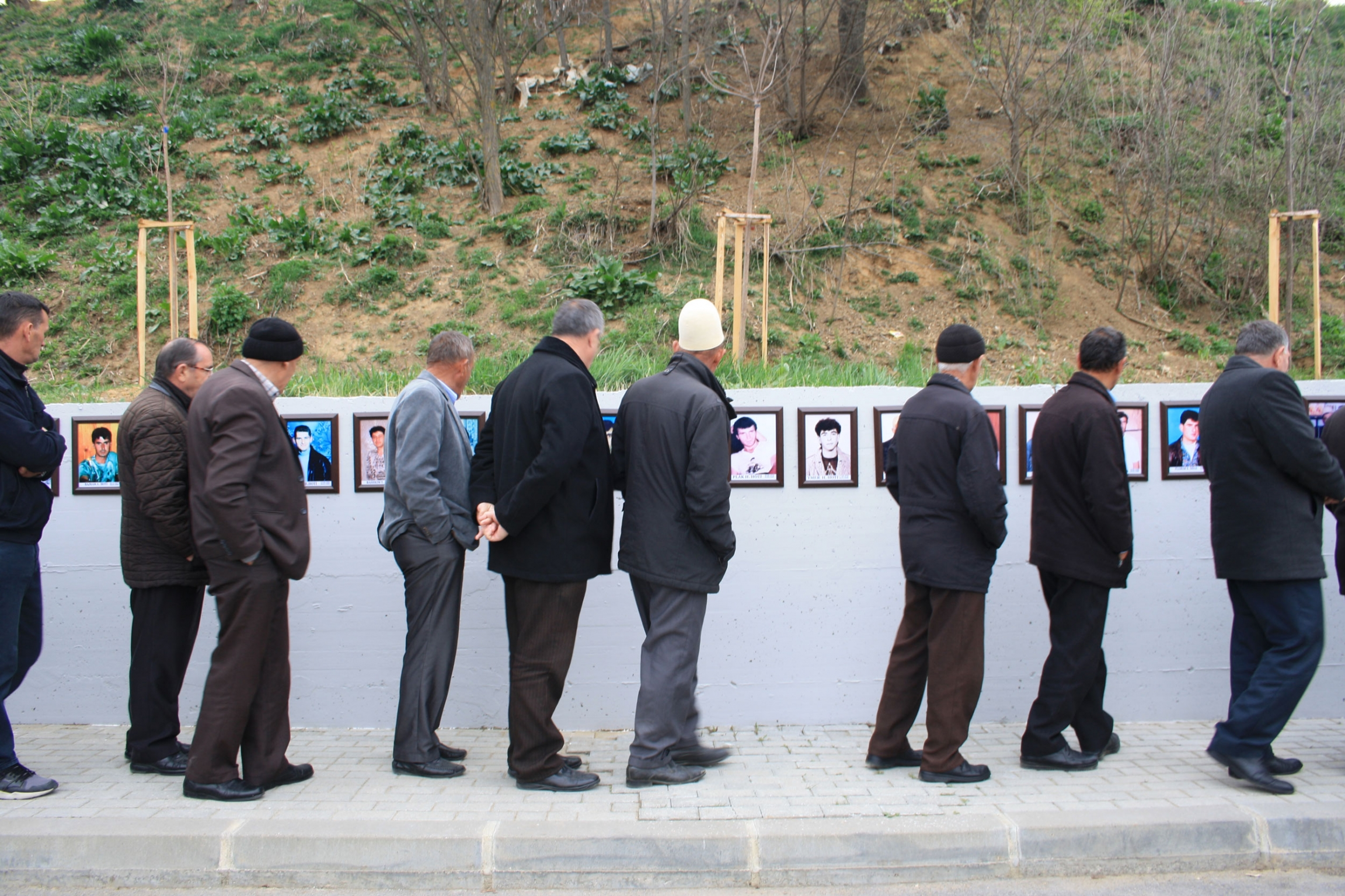 A line of men are shown standing next to a wall with photographs posted on it.