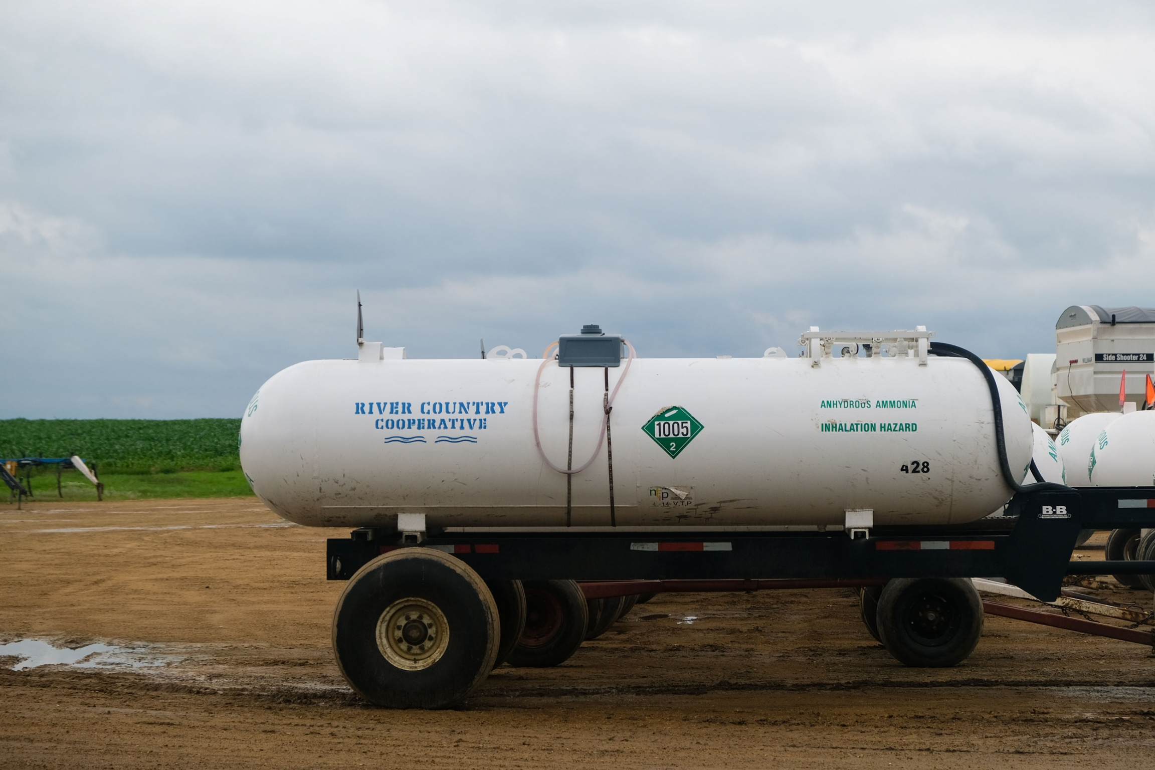 A trailer with a tank of anhydrous ammonia is shown parked on a dirt parking lot.