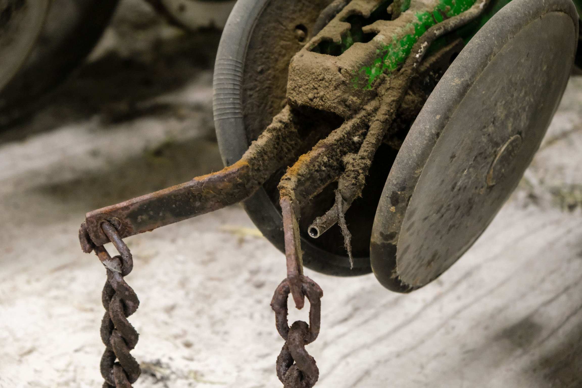 A wheel is shown with rusted metal chains attached and a small tube is connected.