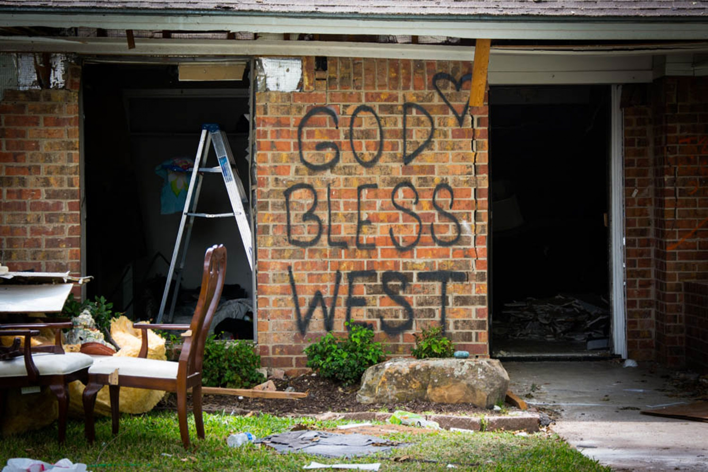 A heavily damaged home is shown with the words, 'God Bless West' spray-painted on it.