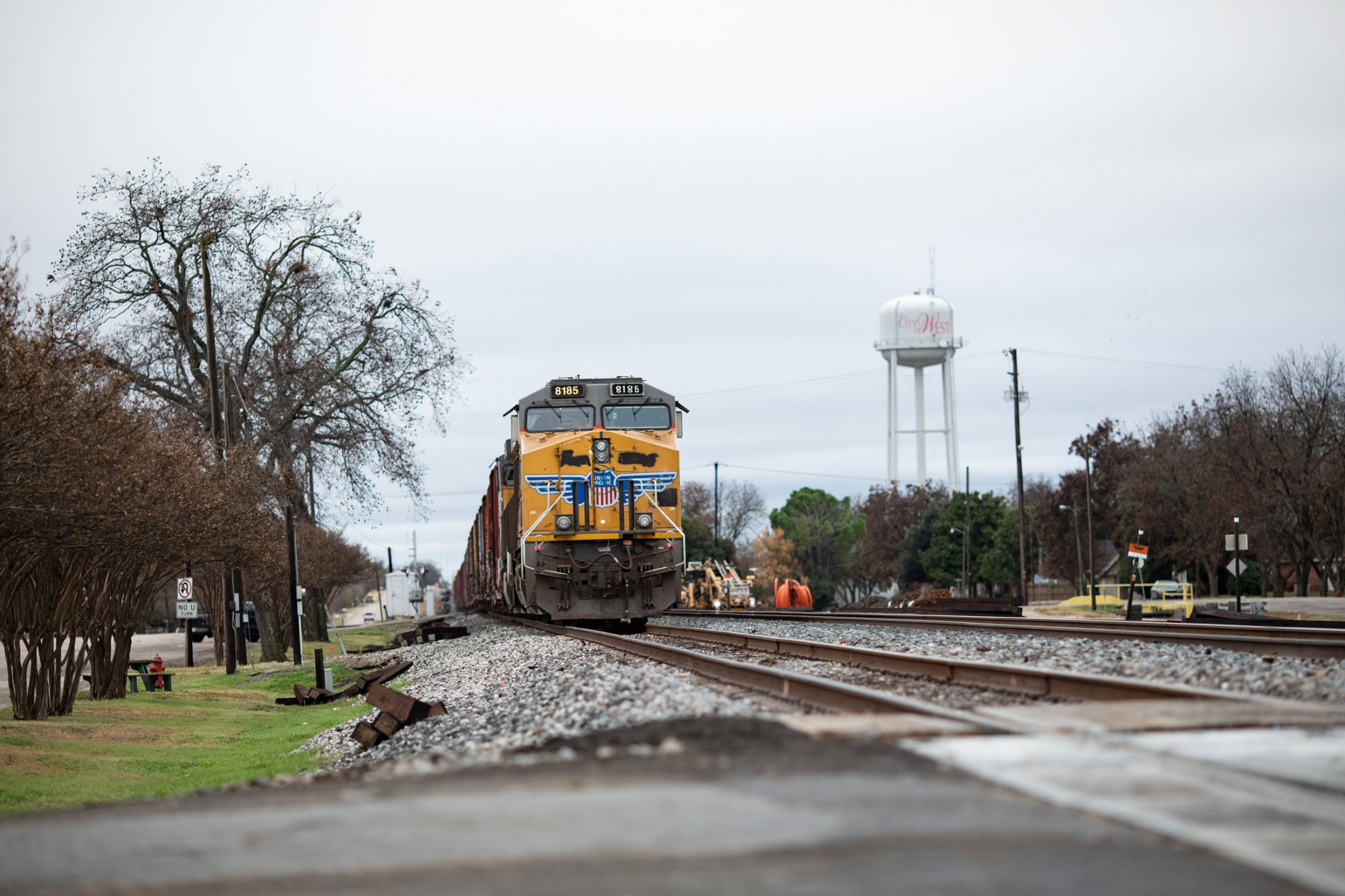 A yellow freight train is shown with a water tower in the background.
