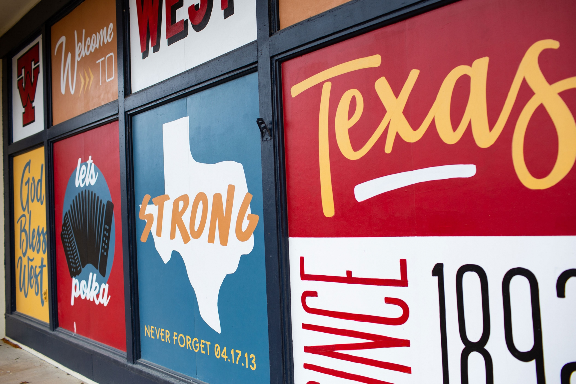 A wall is show with several messages on it, including one that reads, 'Welcome to West, Texas.""