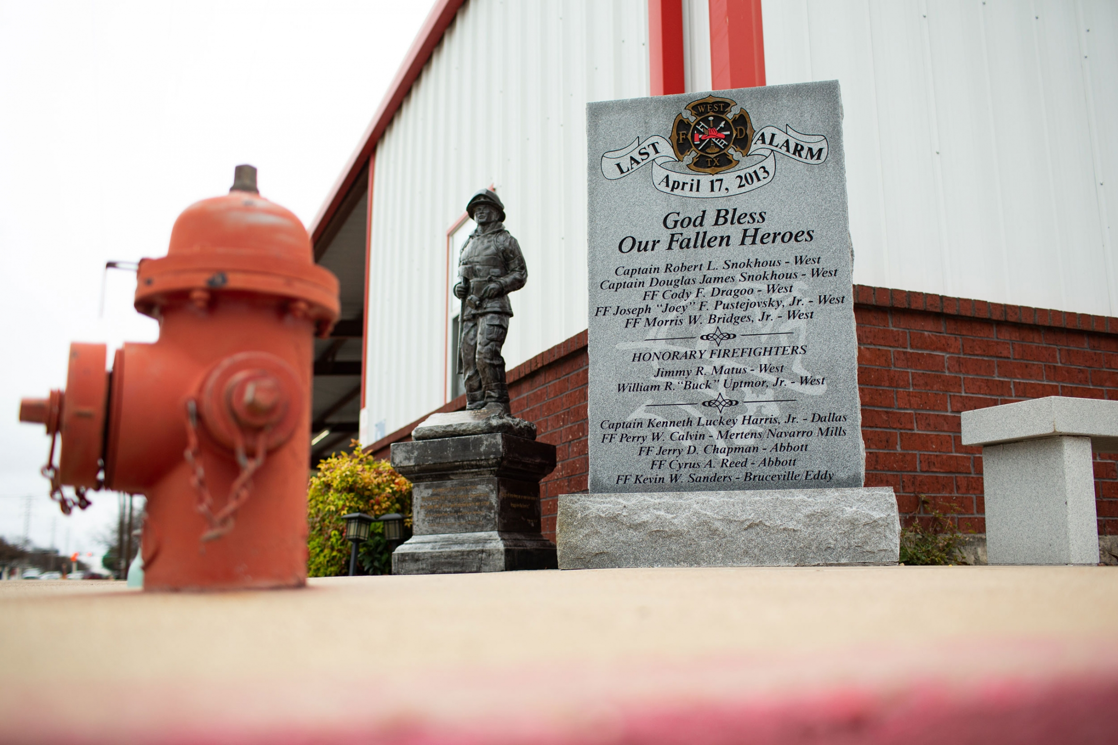 A statue of a fireman is next to a red fire hydrant.