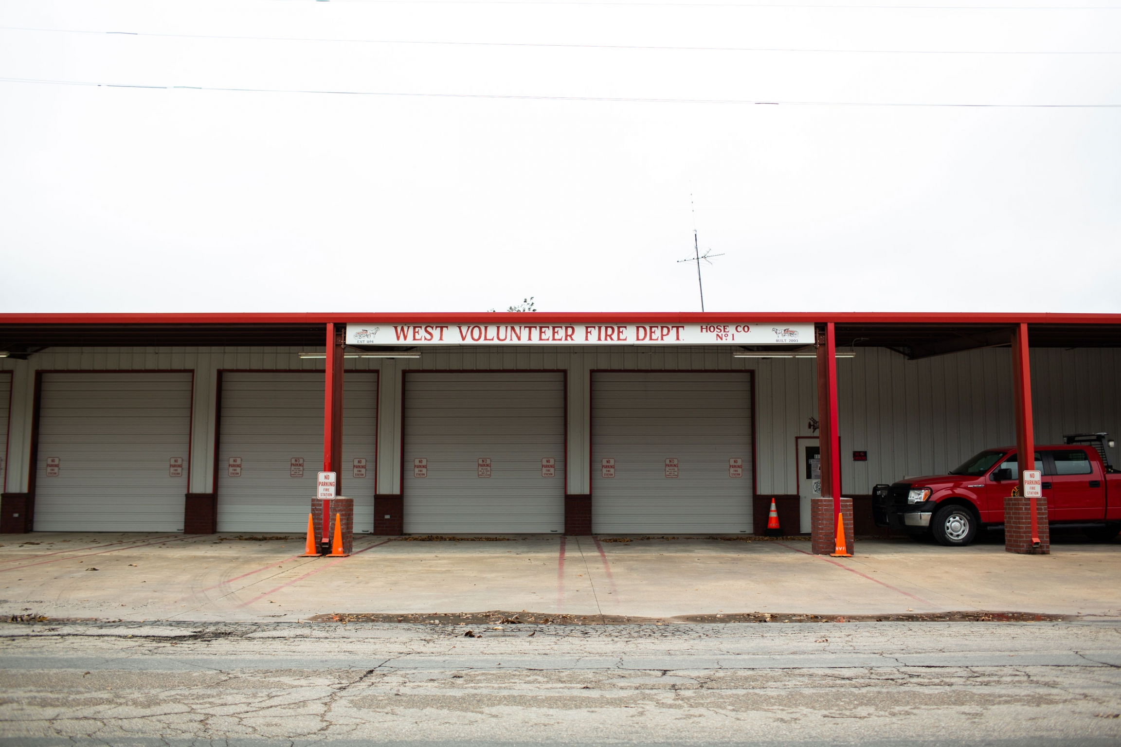 A four bay garage is shown with a red truck on one side.