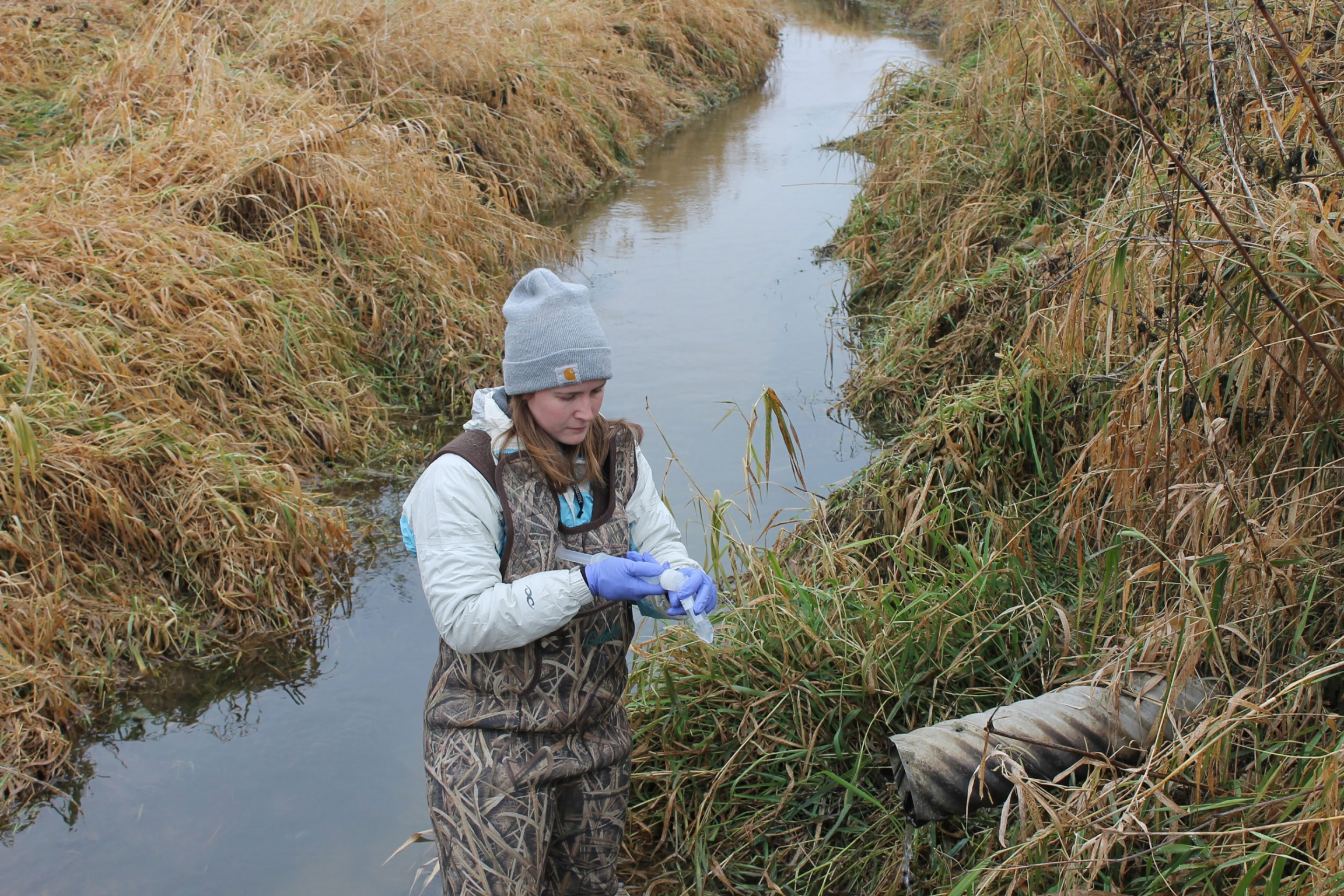 A woman is shown standing in a watery ditch and wearing camoflauge overalls.