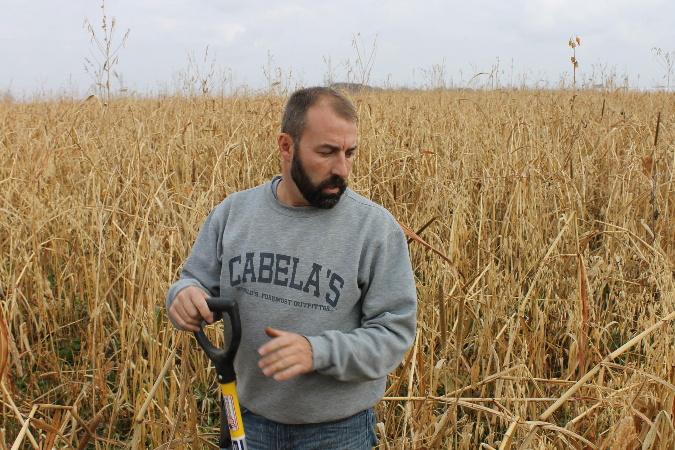 A man is shown wearing a Cabela's sweatshirt and holding a handled-tool.