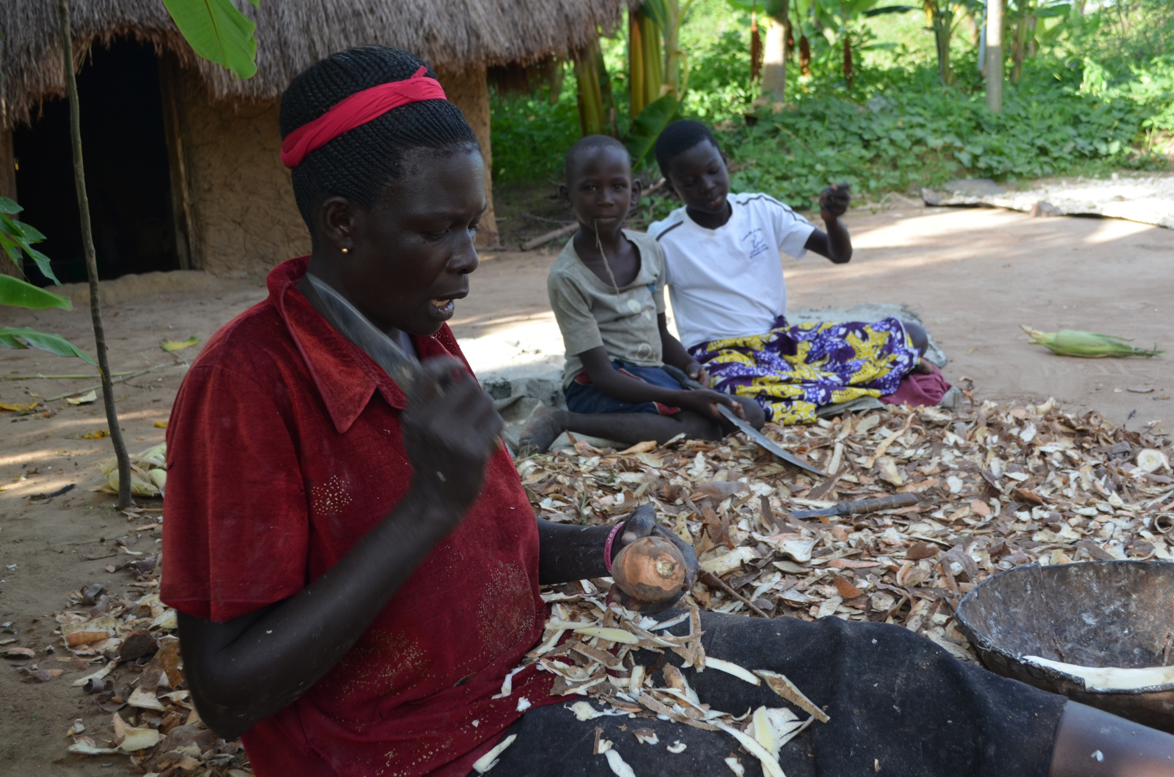 A woman wears a red head band and slices cassava root while sitting on the ground with two children nearby.