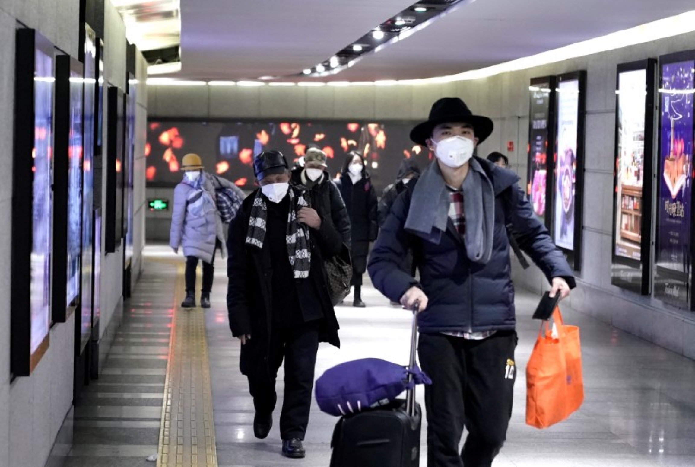People wearing masks walk through an underground passage to the subway in Beijing, Jan. 21, 2020.