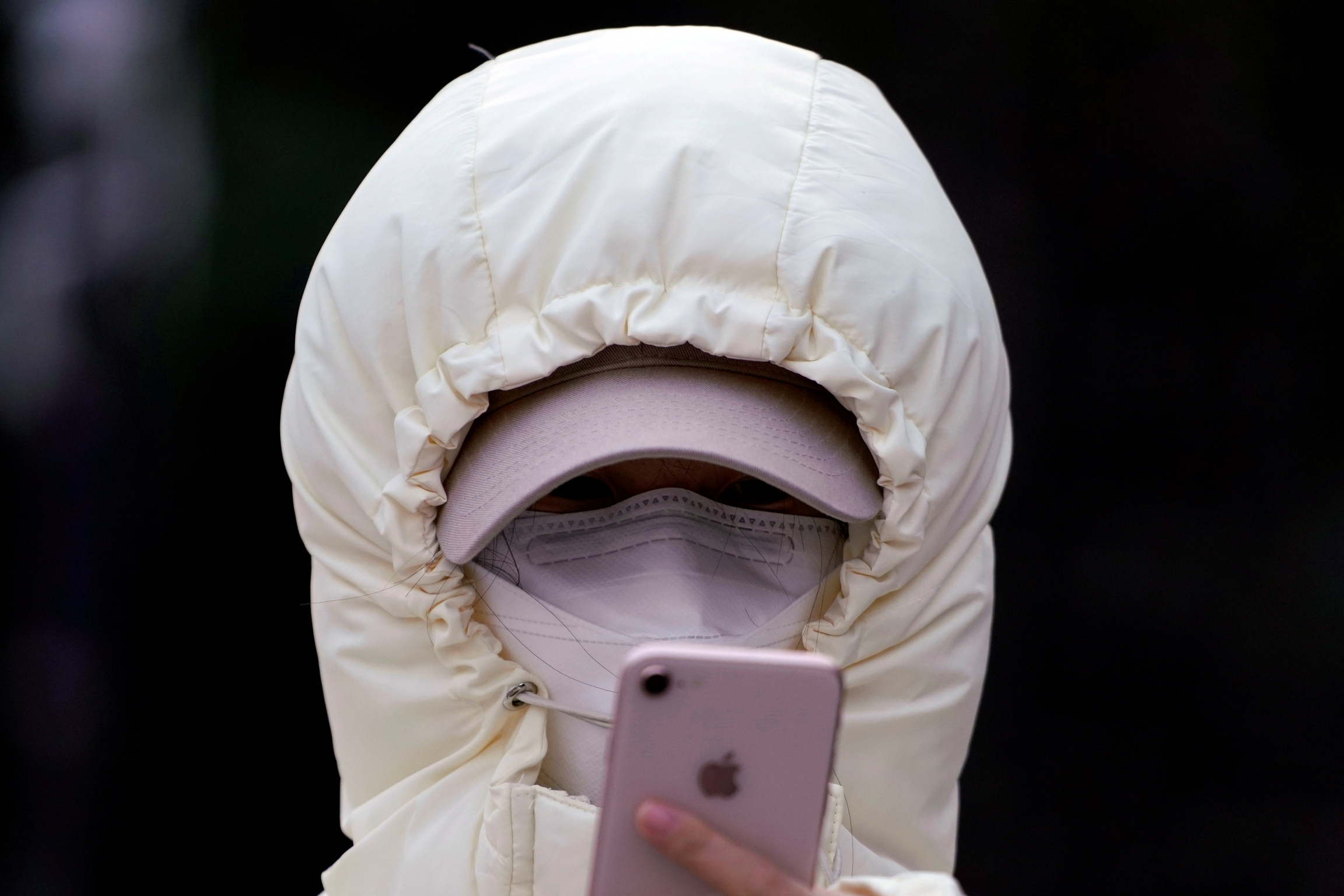 A woman wearing a mask checks her mobile phone in Shanghai, Jan. 29, 2020.