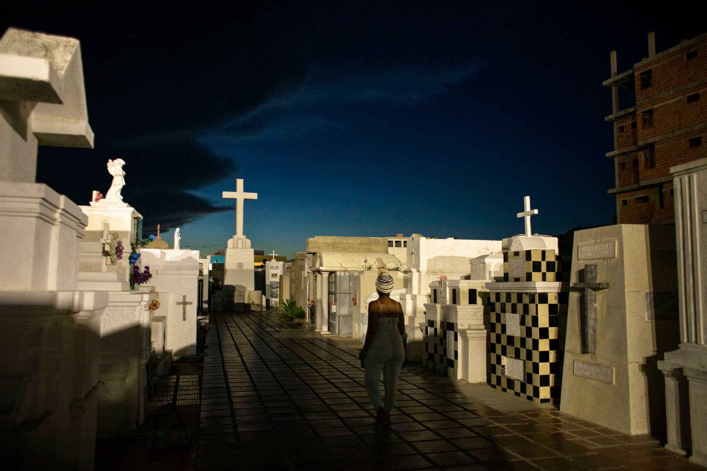 A woman is shown walking in an isle with large tombstones on either side and a white cross at the end.