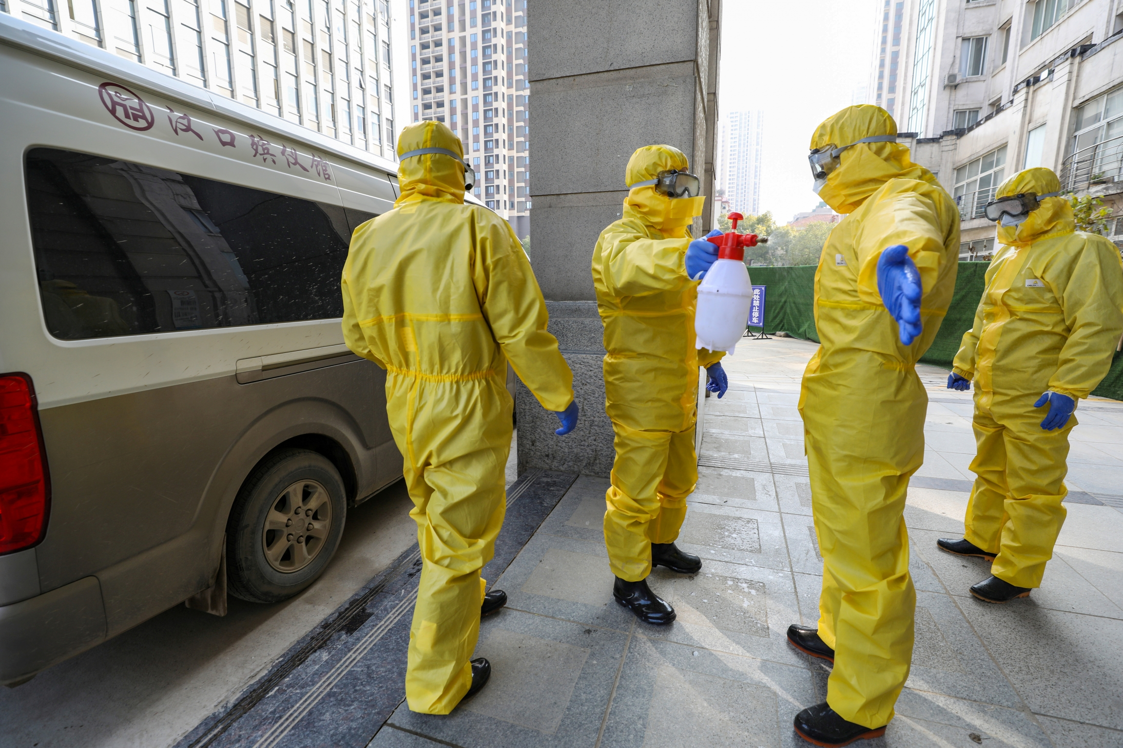 Funeral parlor staff members in protective suits help a colleague with disinfection after they transferred a body at a hospital, following the outbreak of a new coronavirus in Wuhan, Hubei province, China, Jan. 30, 2020.