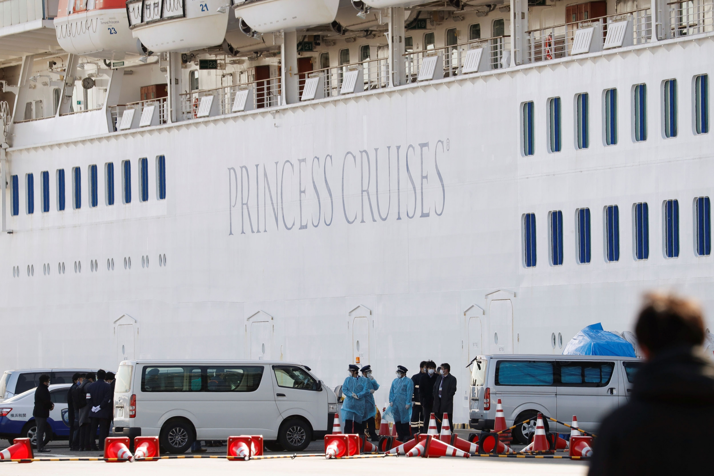 Several vans are shown parked next to a cruise ship with personnel wearing masks stand nearby,
