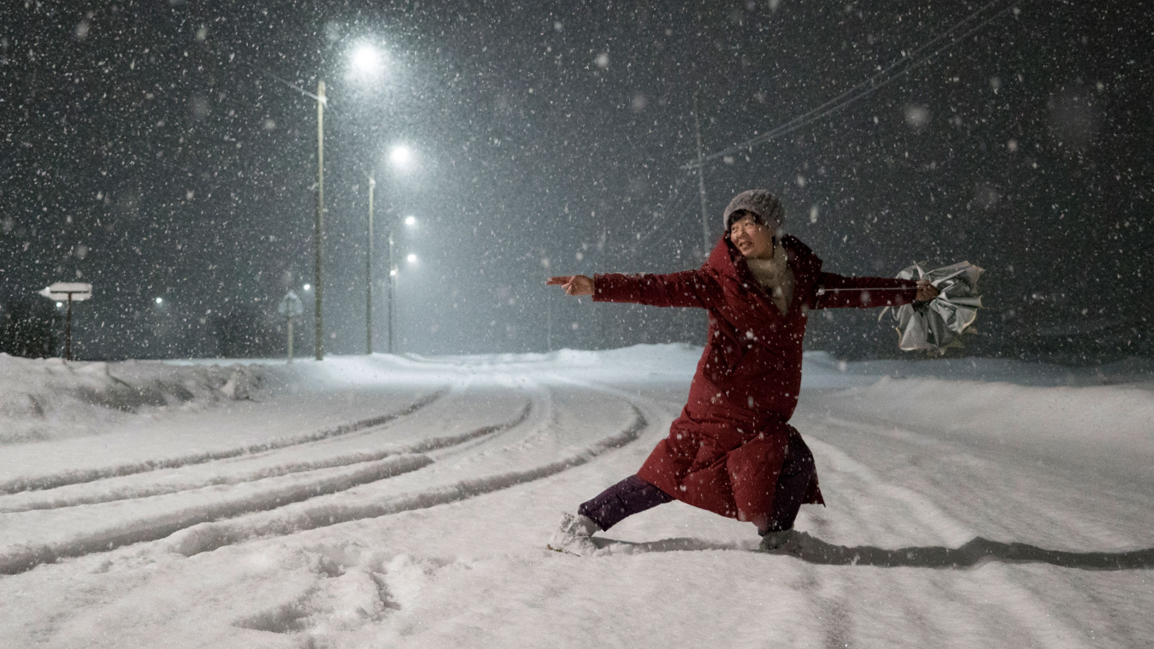 A woman in a red jacket is shown dancing in the street with snow falling all around her.