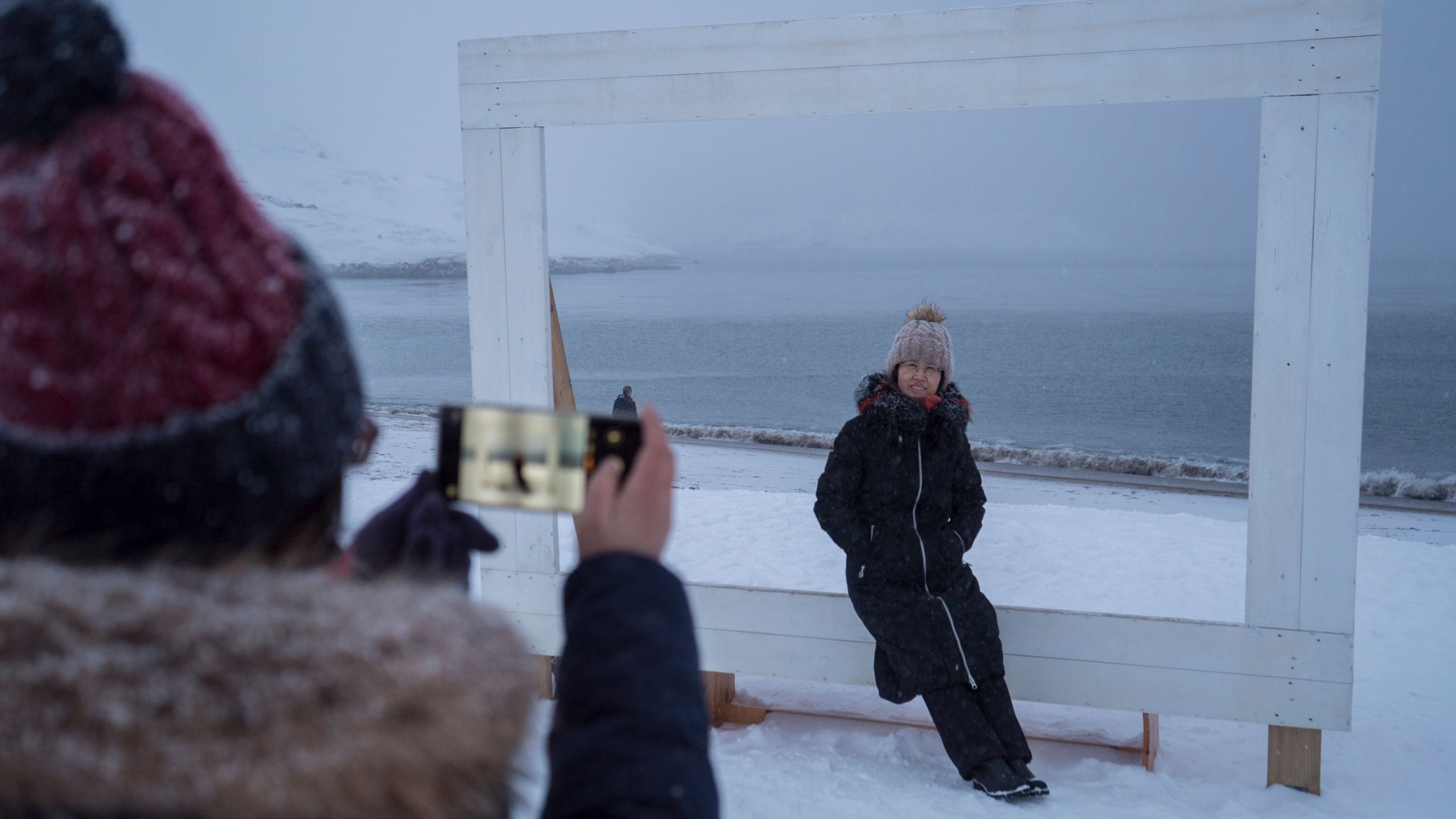 A woman is shown sitting a large frame with the Barents Sea in the background.