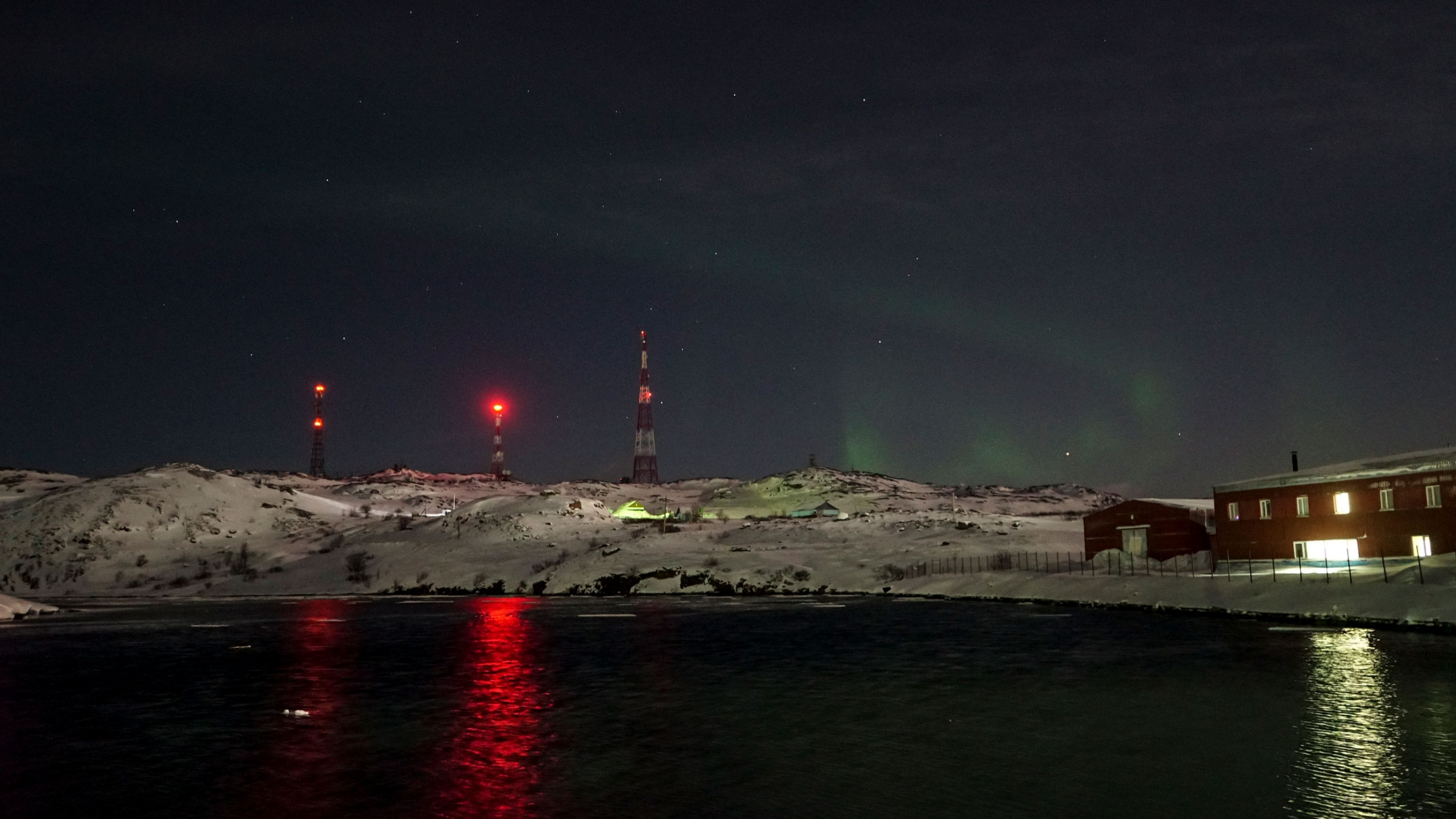 A green swirl of the northern lights is shown against a dark sky with antennas with red lights in the nearground.